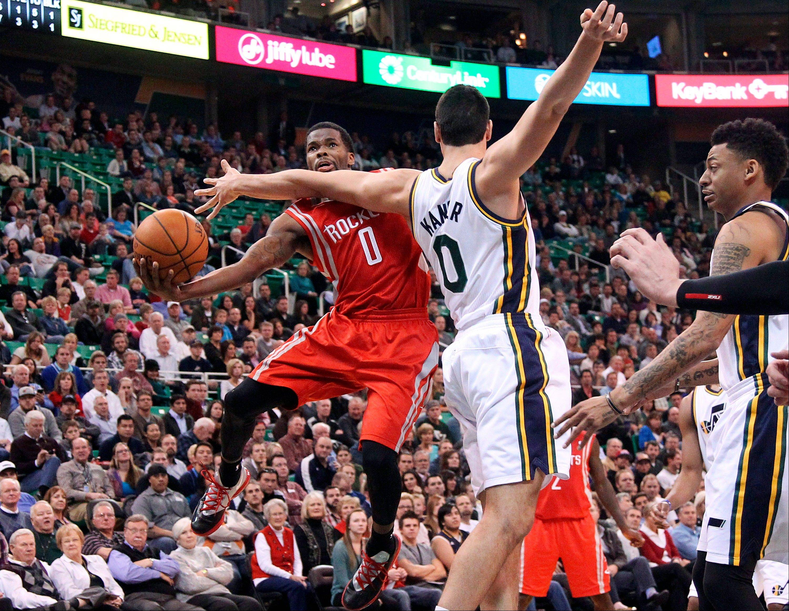 Houston Rockets' Aaron Brooks, left, goes to the basket as Utah Jazz's Enes Kanter (0) defends in the second quarter of an NBA basketball game Monday in Salt Lake City.