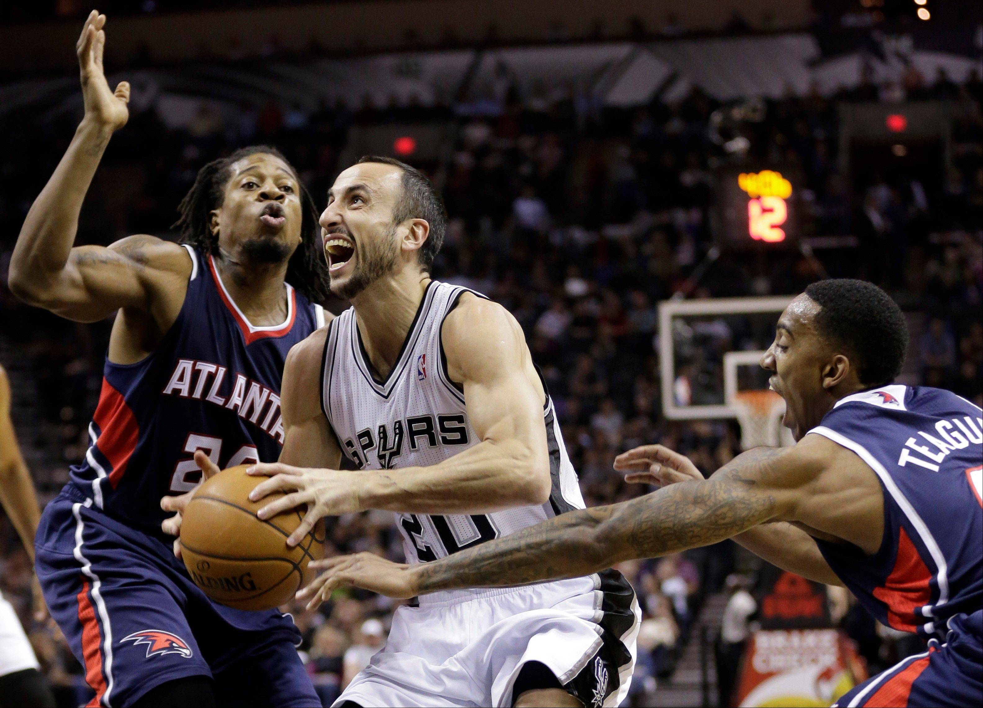 San Antonio Spurs' Manu Ginobili, center, of Argentina, is pressured by Atlanta Hawks' Cartier Martin, left, and Jeff Teague, right, as he drives to the basket during the first half of an NBA basketball game Monday in San Antonio.