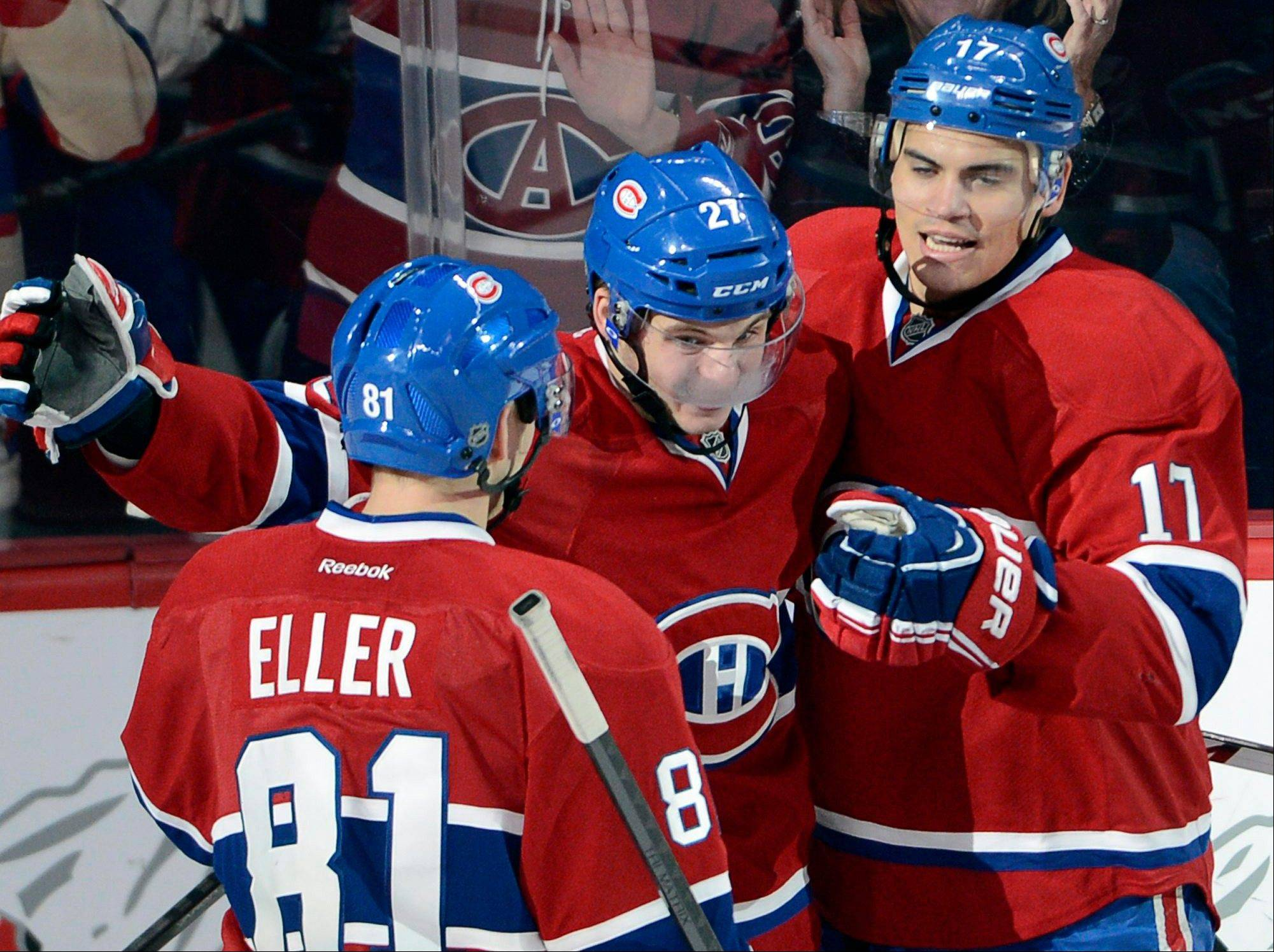 Montreal Canadiens center Alex Galchenyuk (27) celebrates with teammates Lars Eller (81) and Rene Bourque (17) after Galchenyuk scored during the third period of an NHL hockey game Monday in Montreal.