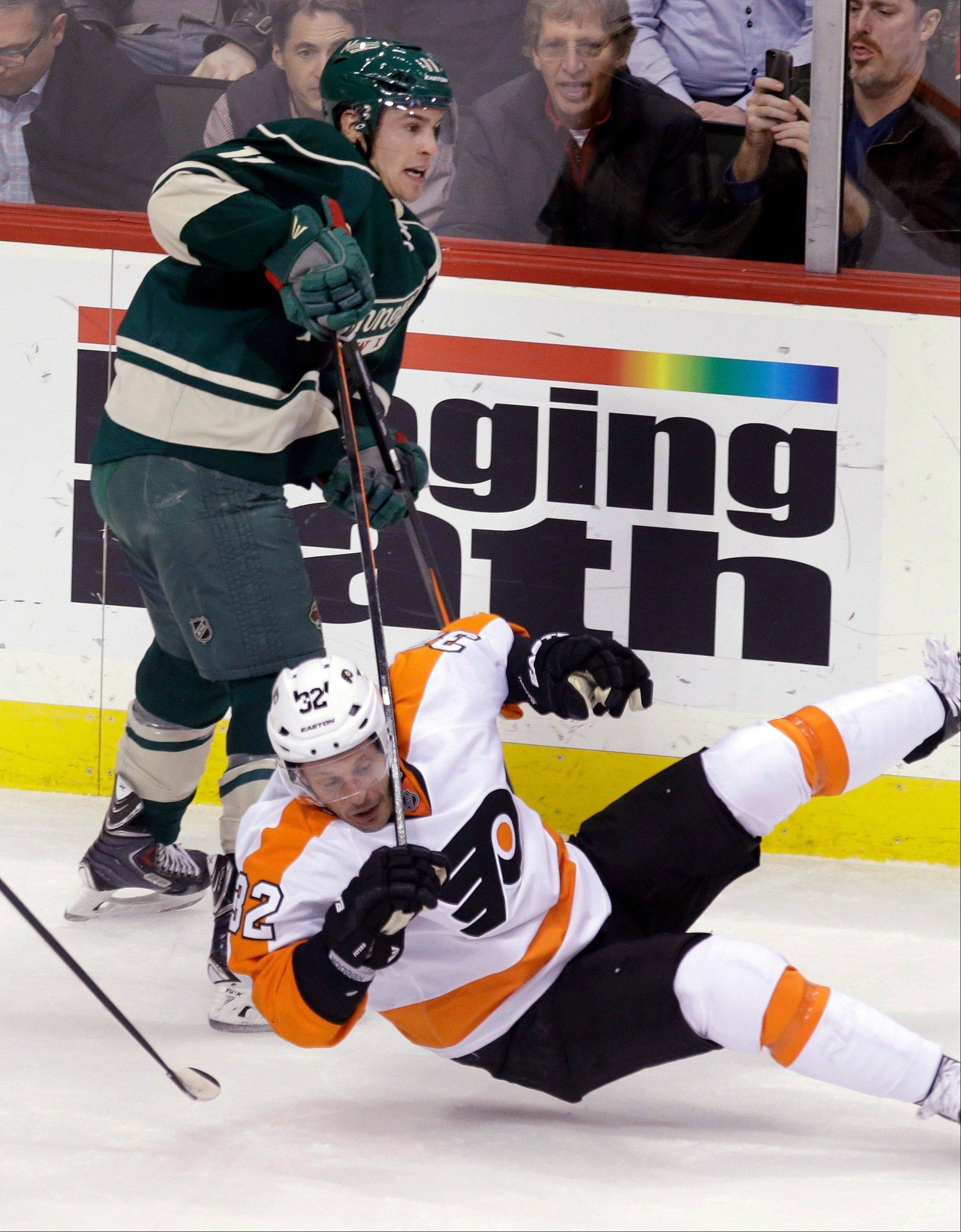 Minnesota Wild�s Zach Parise, top, sends Philadelphia Flyers defenseman Mark Streit to the ice in the first period of an NHL hockey game Monday in St. Paul, Minn.