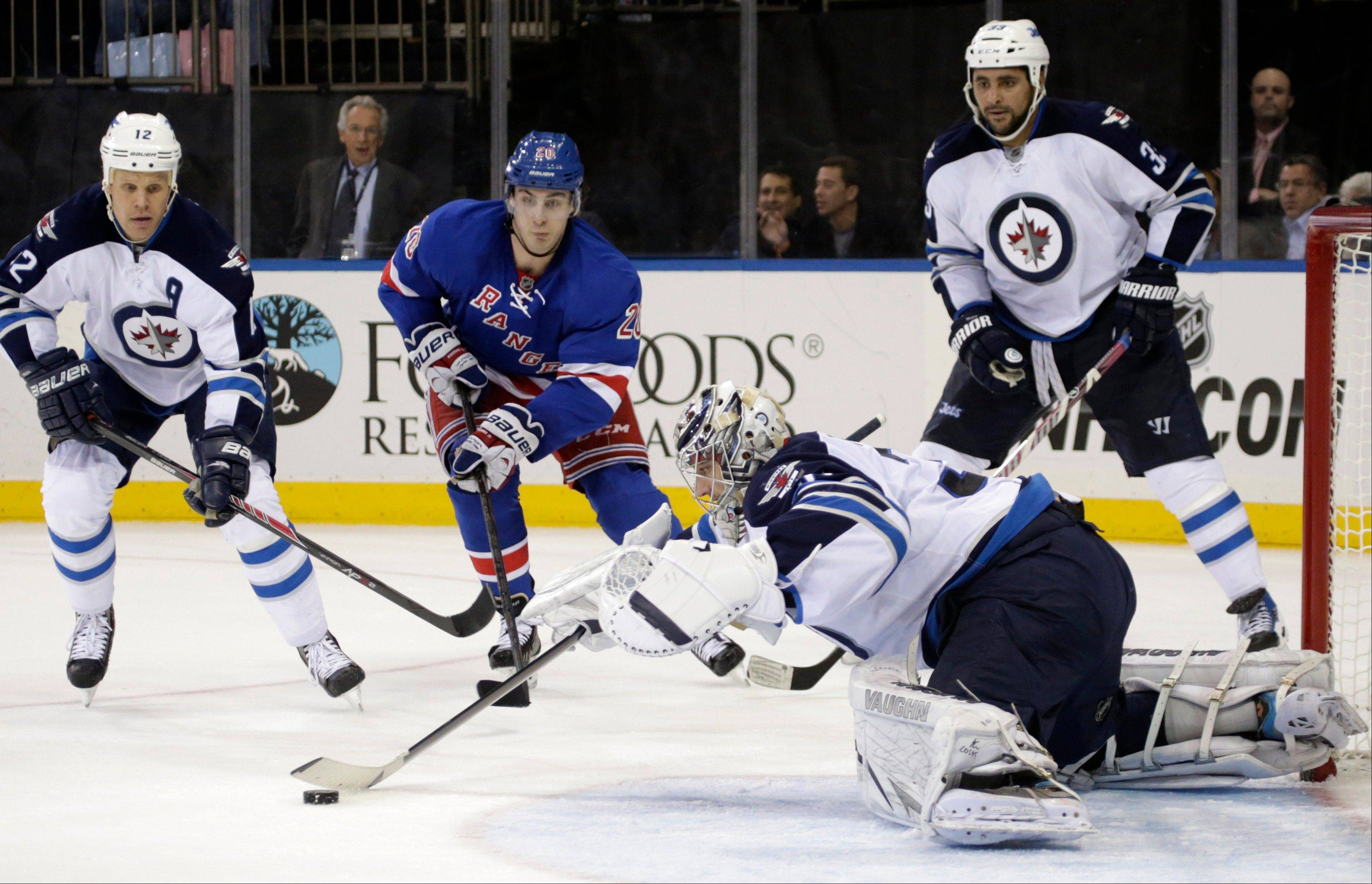 Winnipeg Jets goalie Ondrej Pavelec (31) of the Czech Republic makes a save as Winnipeg Jets center Olli Jokinen (12) of Finland defends and New York Rangers left wing Chris Kreider (20) skates toward the goal in the second period of their NHL hockey game Monday in New York.