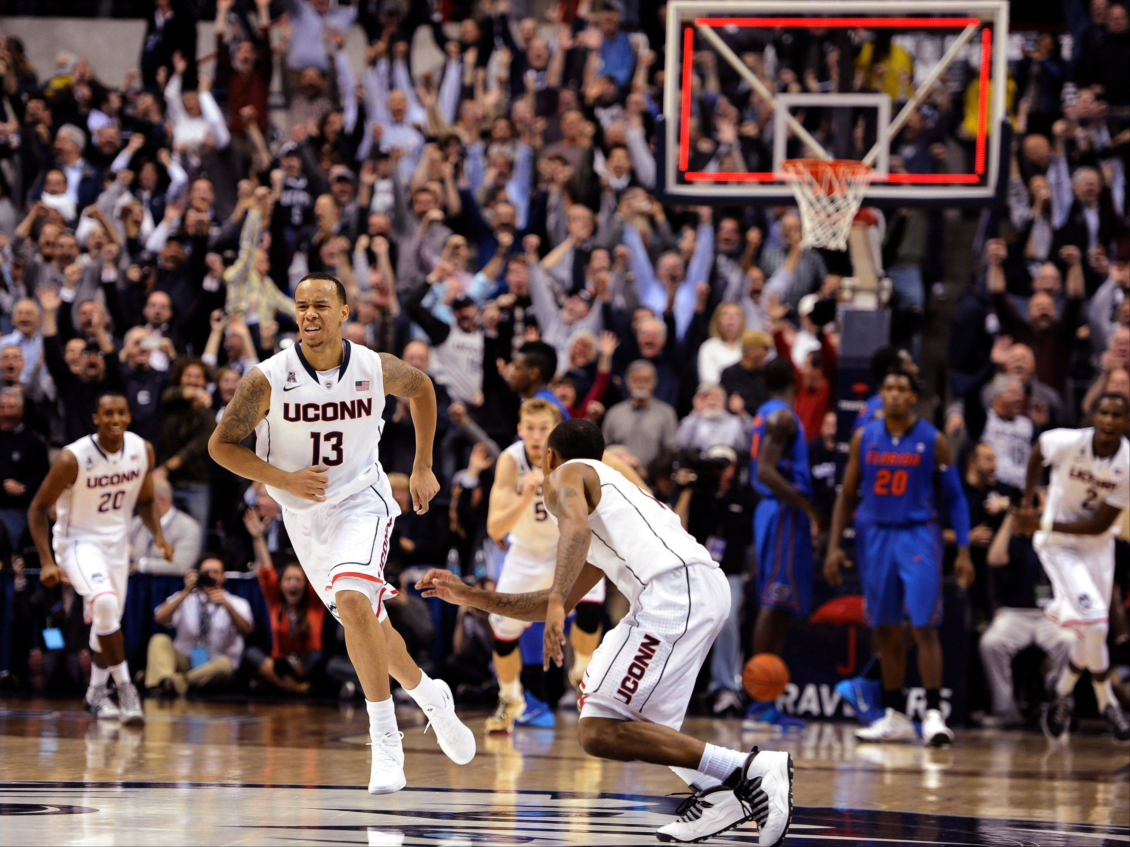 Connecticut's Shabazz Napier, left, and Ryan Boatright, right, react after Napier hits the game winning basket at the end an NCAA college basketball game Monday against Florida in Storrs, Conn. Connecticut won 65-64.