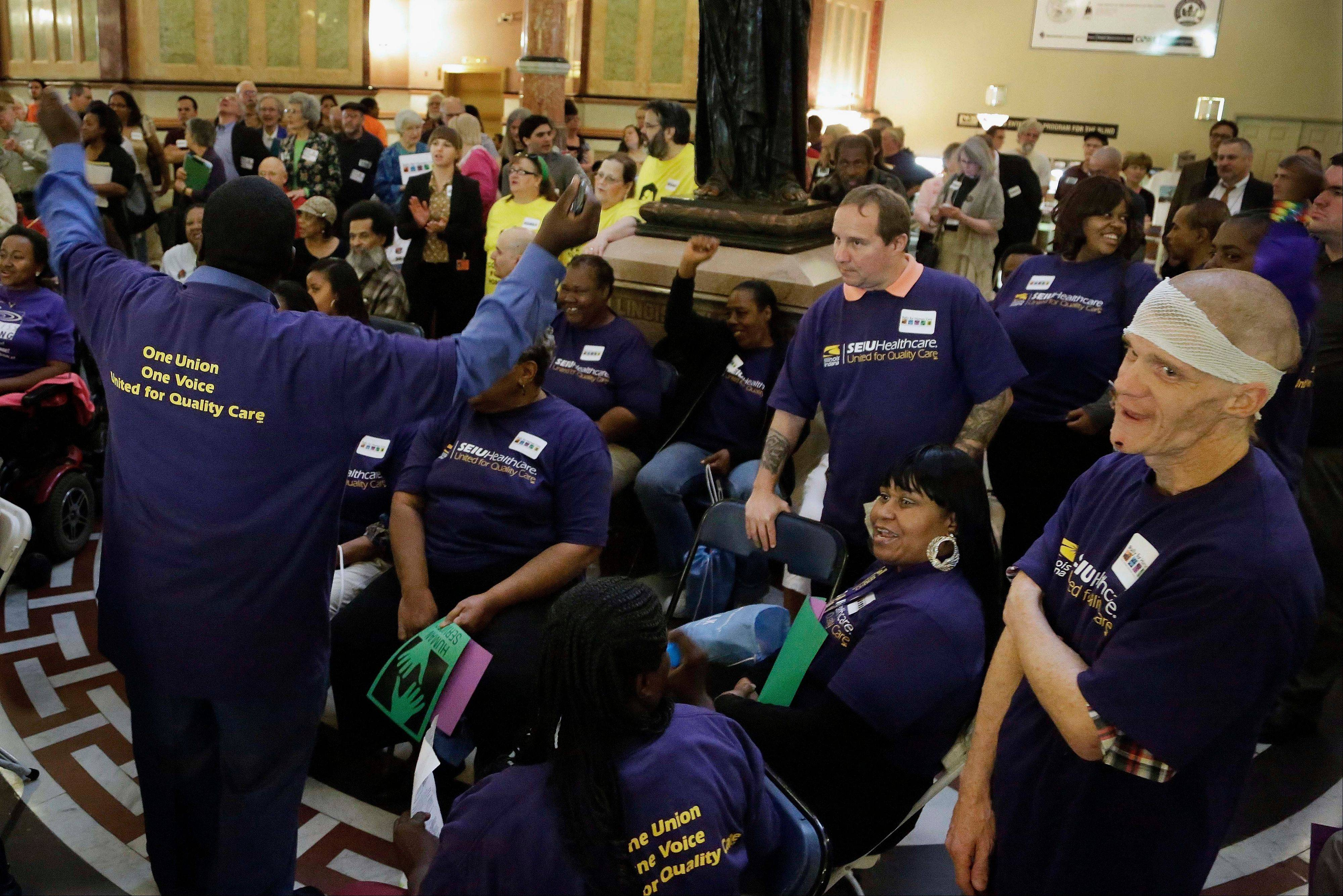 In this May 8, 2013 photo, Service Employees International Union members rally in the capitol rotunda before a Senate hearing on pension legislation at the state Capitol in Springfield