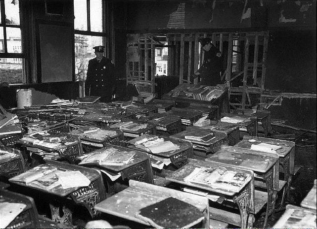 Officials inspect Sister M. Clare Therese Champagne's classroom after the 1958 fire at Our Lady of the Angels. Twenty-seven of 55 students in the classroom perished.