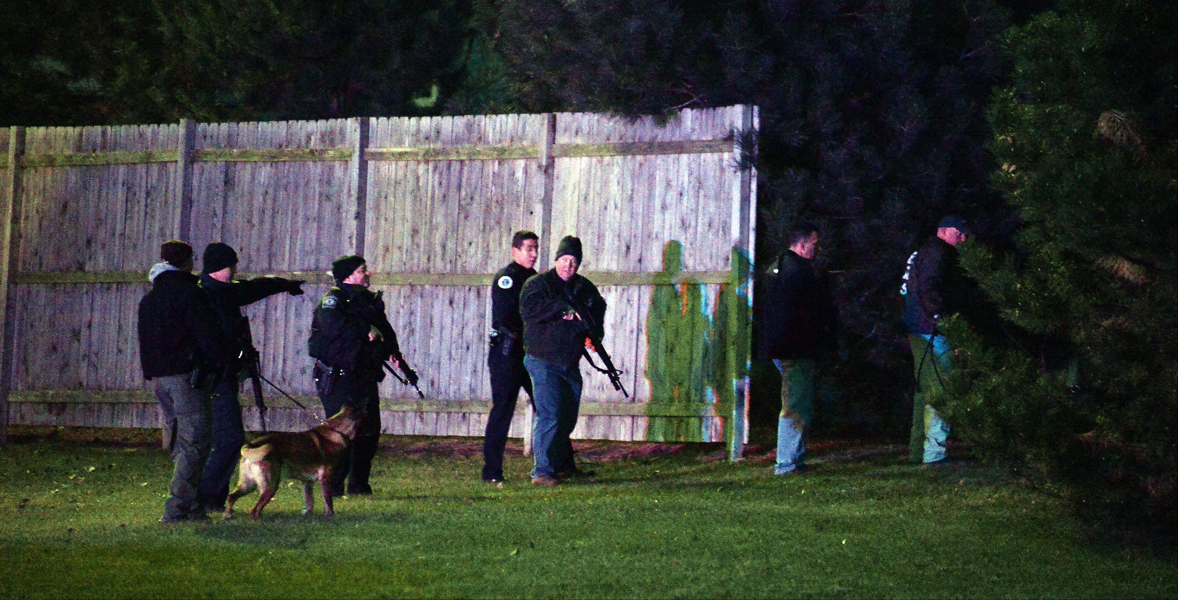 Palatine police and the sheriff's department with their dogs search the yards behind the Chase bank in palatine after and afternoon bank robbery.
