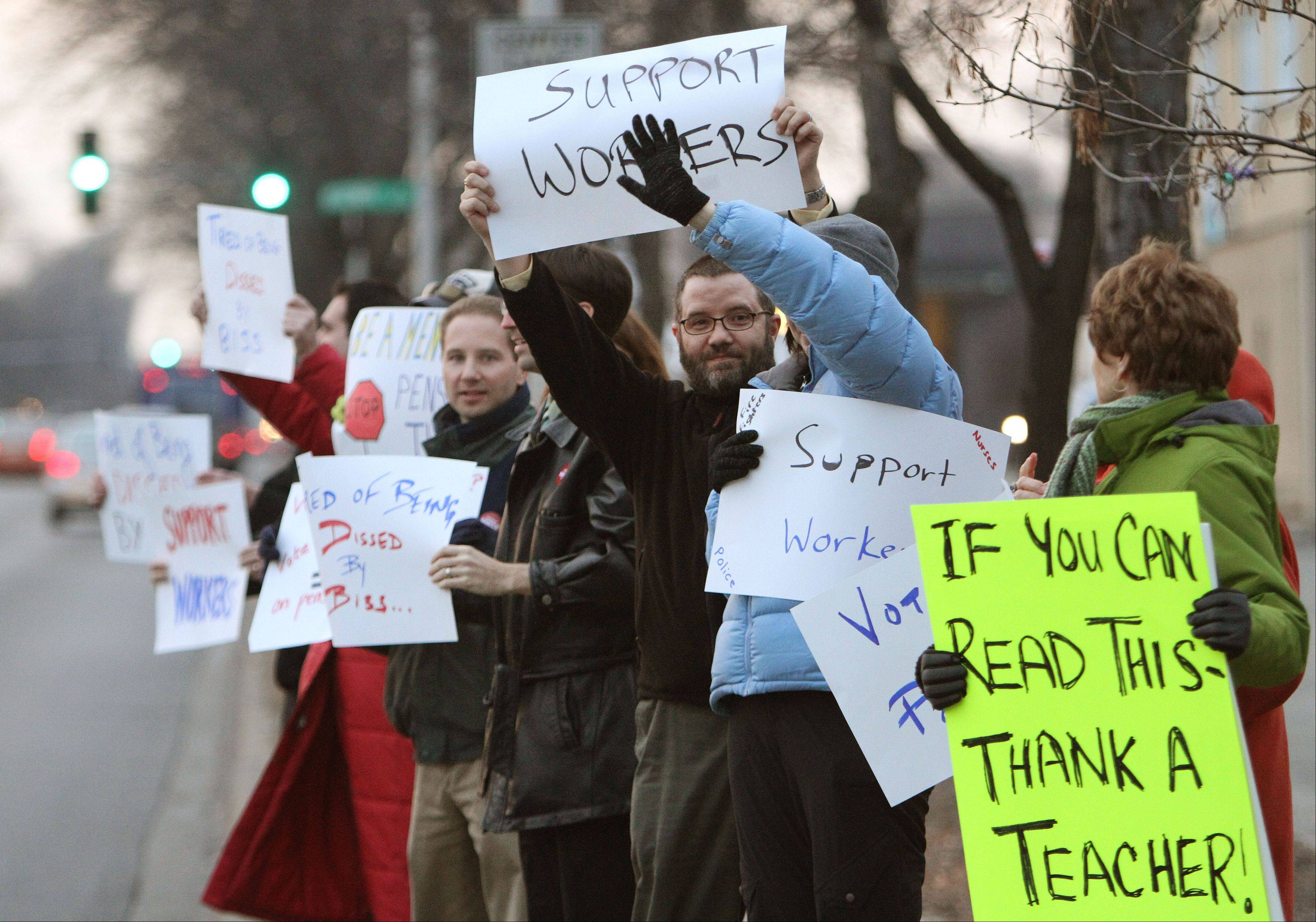 About 40 teachers and retirees protested against proposed state employee pension cuts outside the office of state Sen. Daniel Biss in Skokie.