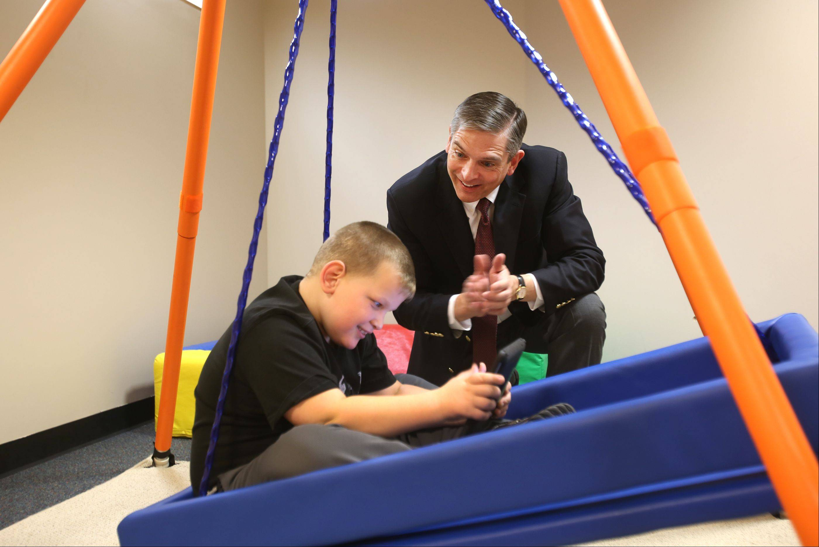 Gilbert Fonger, Marklund's president and CEO, observes Bartosz K. who uses an iPad in his platform therapy swing at the Marklund's Life Skills Academy in Bloomingdale.