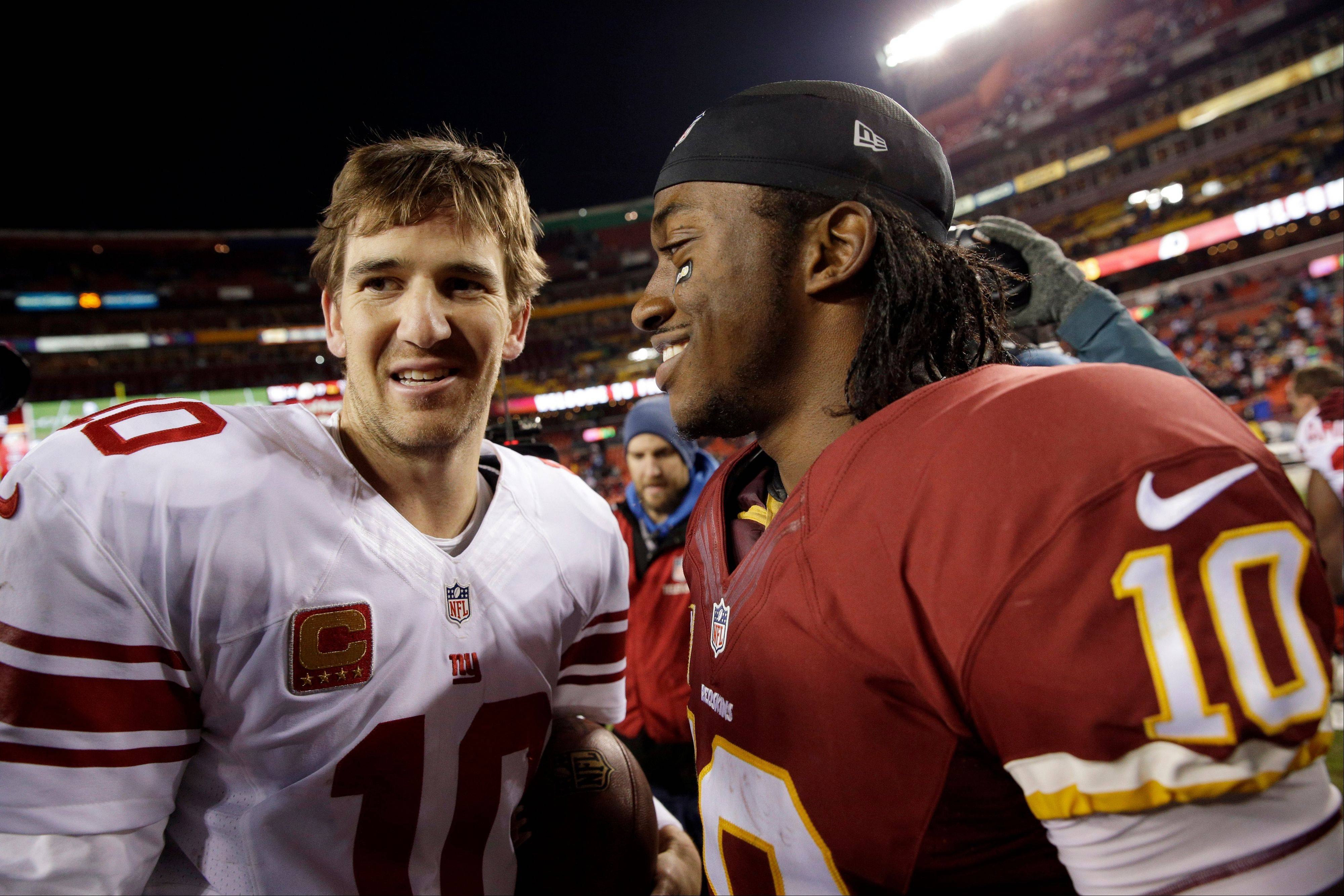 New York Giants quarterback Eli Manning, left, talks with Washington Redskins quarterback Robert Griffin III after the game Sunday in Landover, Md.
