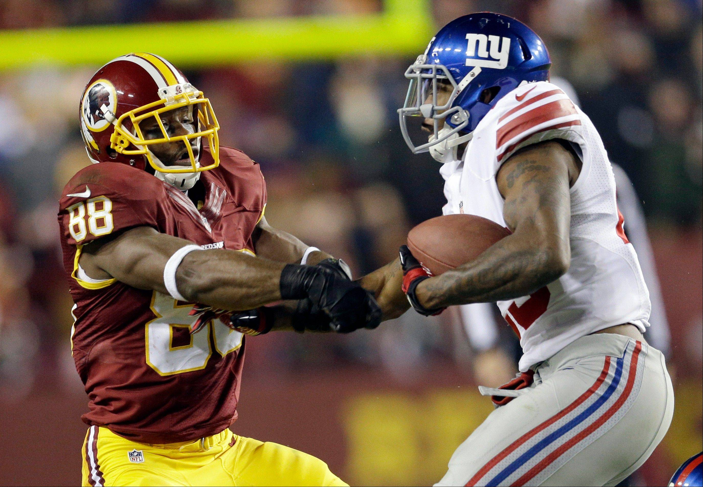 New York Giants free safety Will Hill, right, takes the football away from Washington Redskins wide receiver Pierre Garcon (88) during the second half of an NFL football game Sunday in Landover, Md.