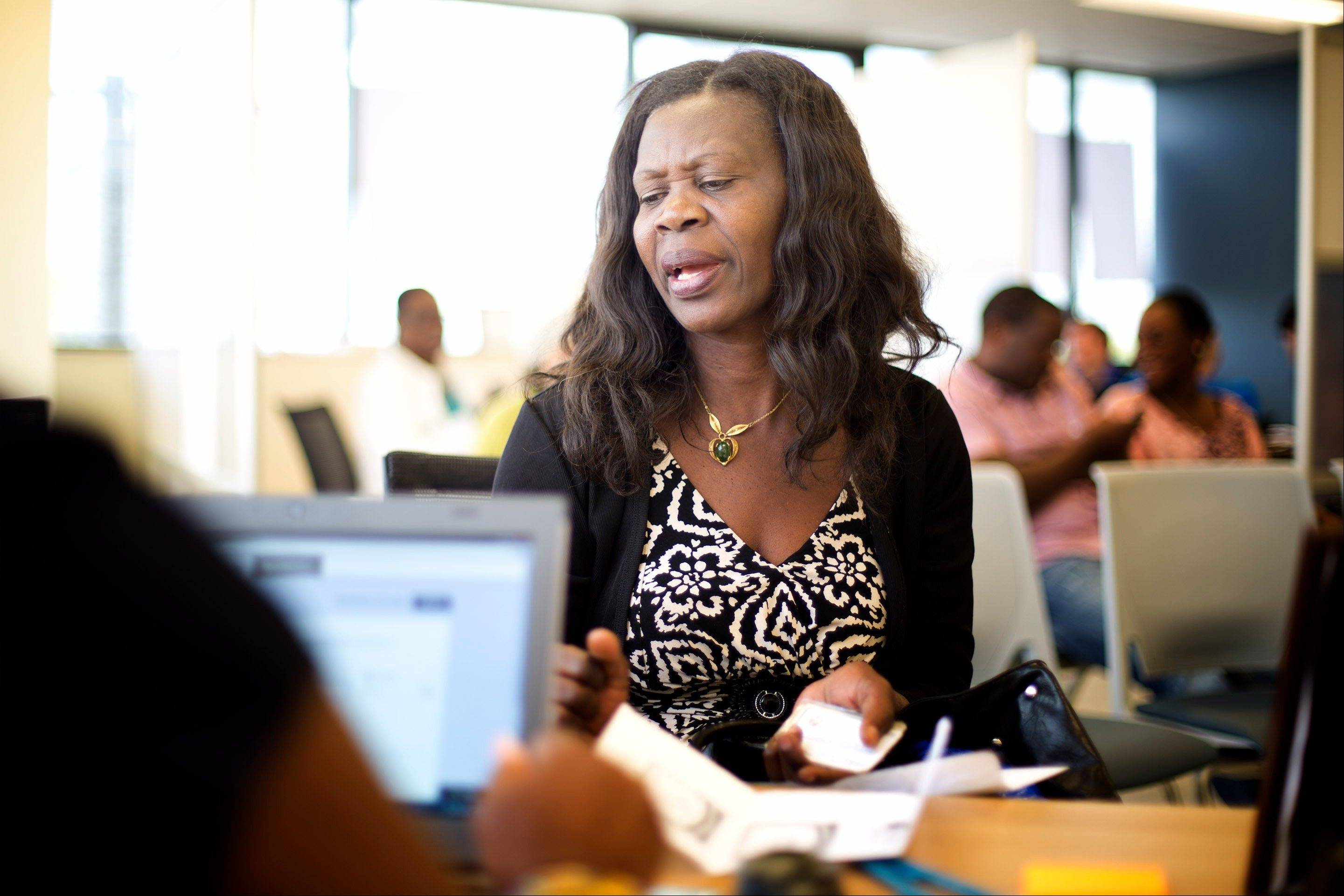 Gina Denis, now seen, a certified counselor at Miami�s Boringuen Health Center, works with an unidentified client, signing her up for Obama Care, Monday, Dec. 2, 2013.