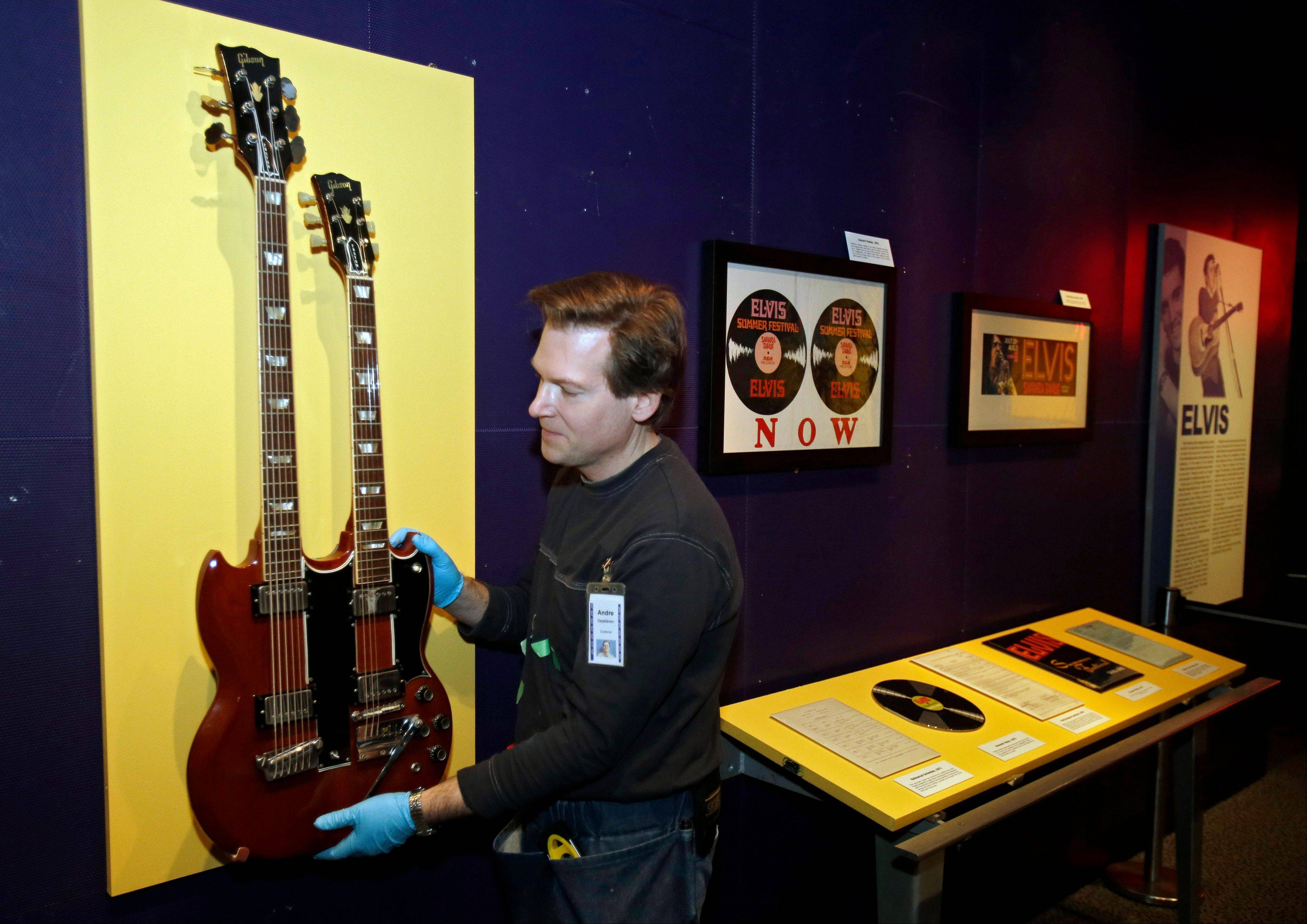Andre Sepetavec installs a double-necked guitar in the Elvis exhibit at the Rock and Roll Hall of Fame and Museum in Cleveland.