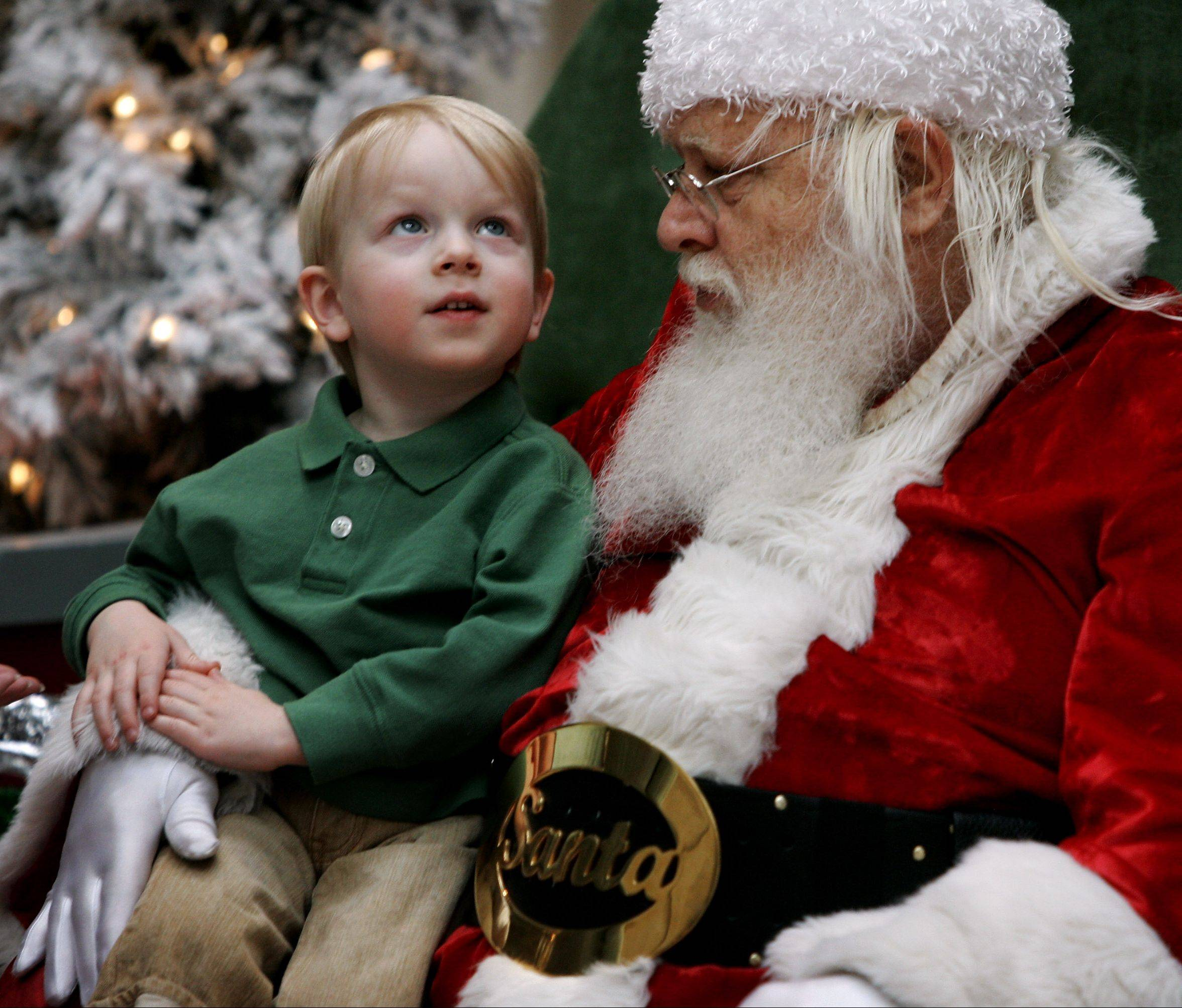 Santa Claus listens to Owen Arnold, 3, of Riverwoods as he tells him what he wants for Christmas at Westfield Hawthorn Shopping Center in Vernon Hills. Avoid shooting the standard picture of everyone smiling at the camera and wait for the better moment when children interact with Santa Claus and capture a memory that will last much longer.
