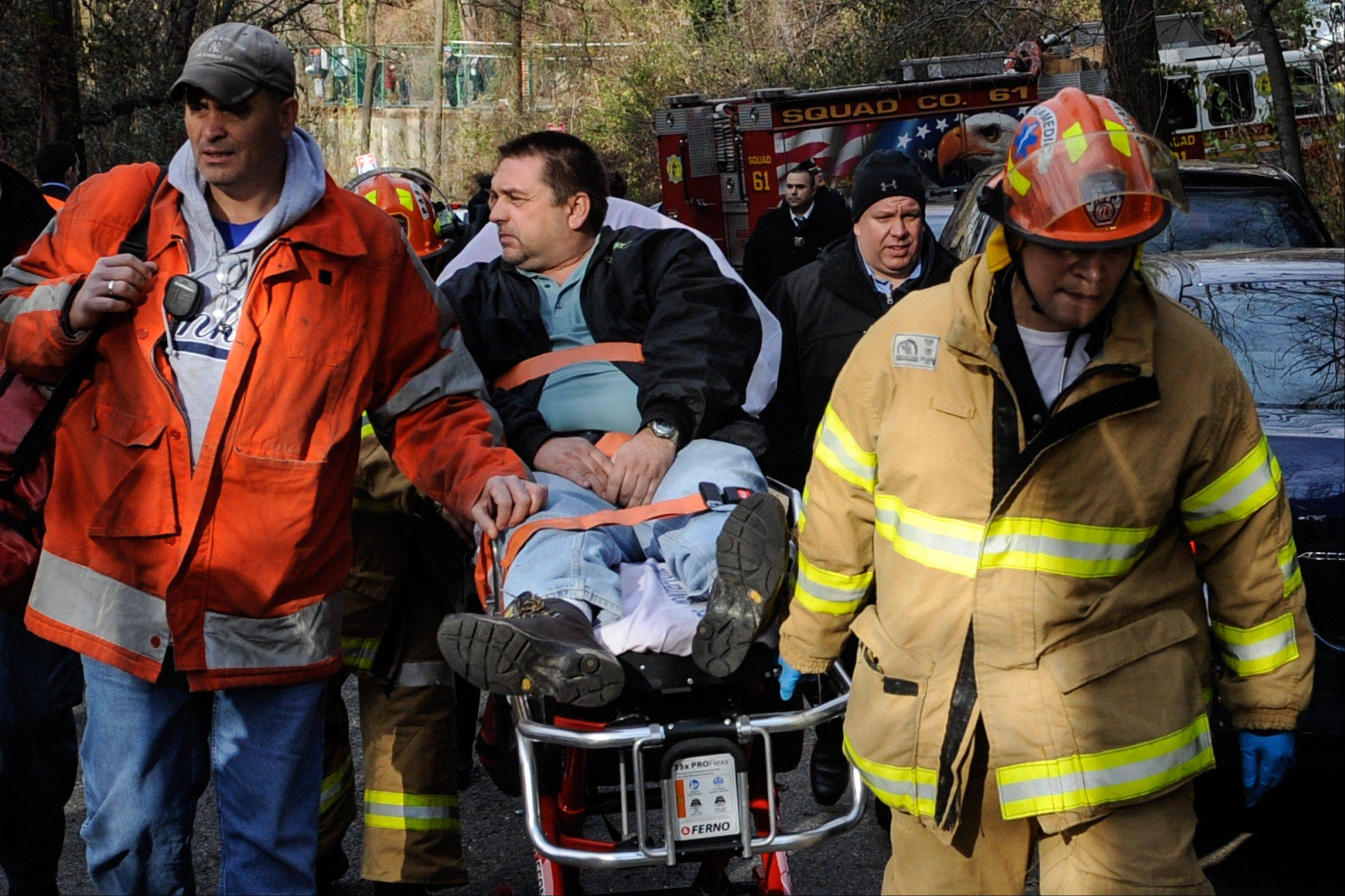 In this photo taken on Sunday, Metro North Railroad engineer William Rockefeller is wheeled on a stretcher away from the area where the commuter train he was operating derailed in the Bronx borough of New York. The National Transportation Safety Board reported Monday that the train Rockefeller was driving was going 82 mph around a 30-mph curve when it derailed killing four people and injuring more than 60.