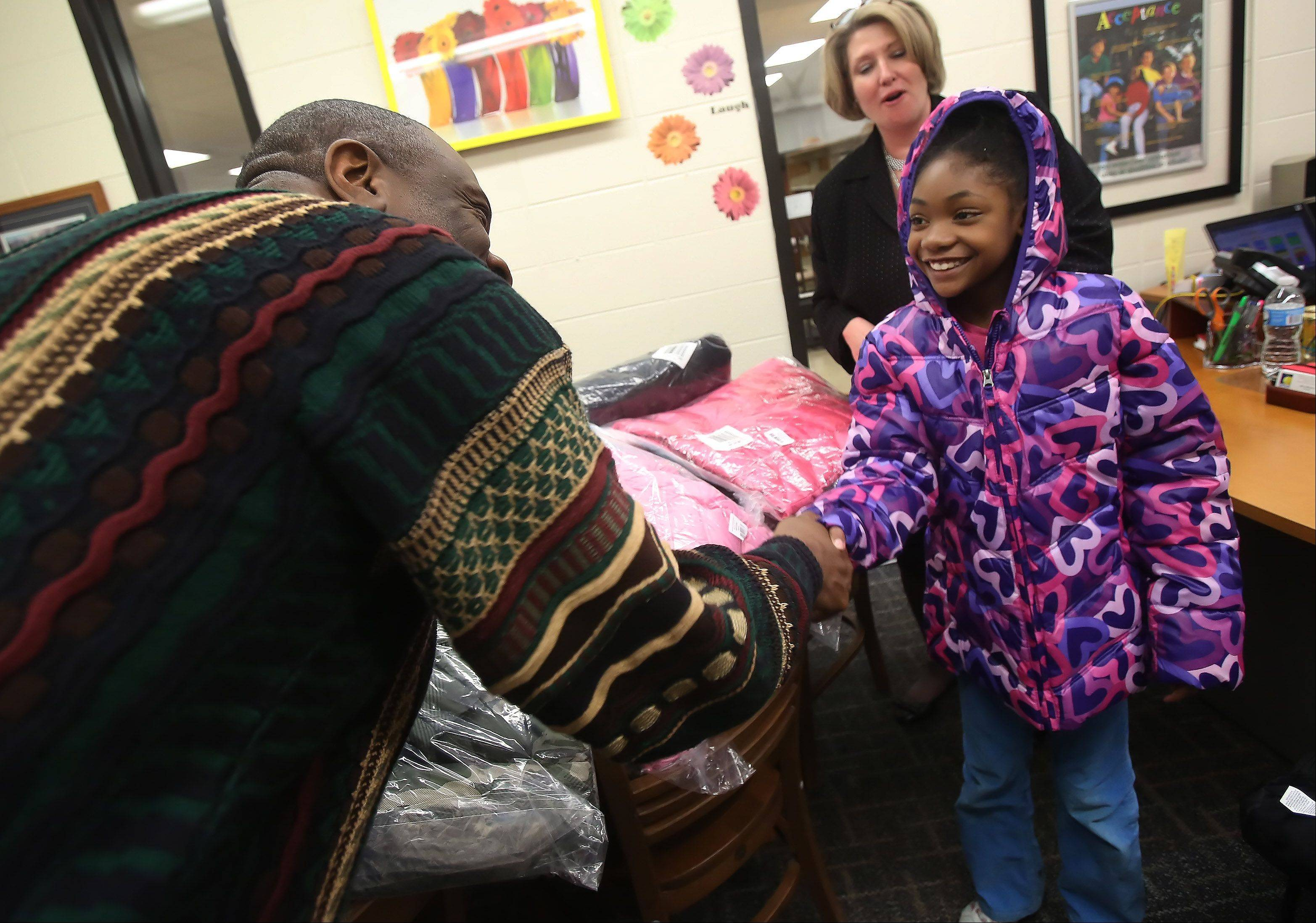 Raymond Ellis Elementary School third-grader Tahirah Young thanks Pastor Choice Harris after receiving a new coat Tuesday at the Round Lake Beach school. Christian Faith Fellowship Church Round Lake donated 50 coats to the school during its first winter coat drive.
