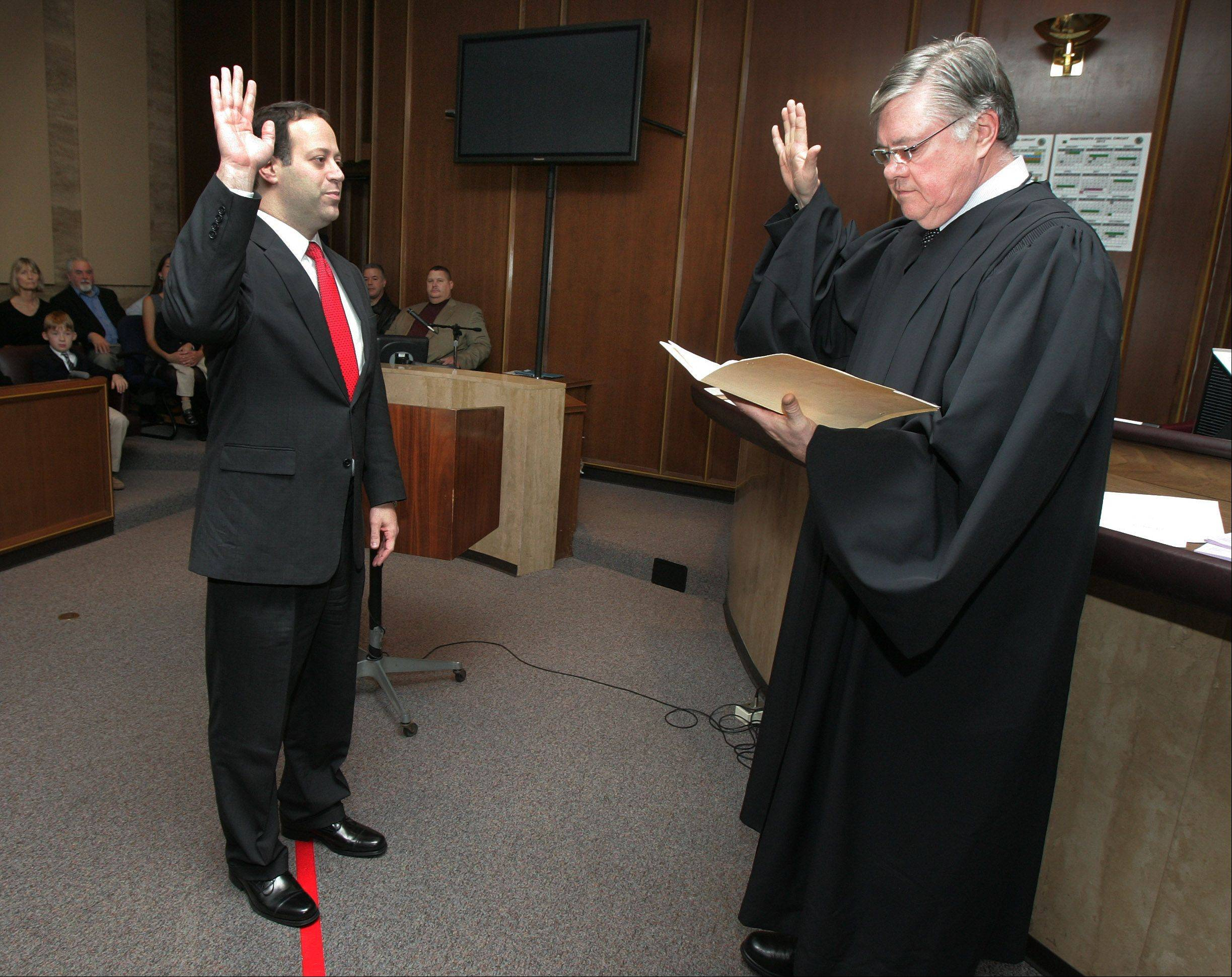 Keith Brin is sworn in by Chief Judge Fred Foreman, right, as the new Lake County circuit court clerk last year. Foreman announced Tuesday that he�ll retire in January.
