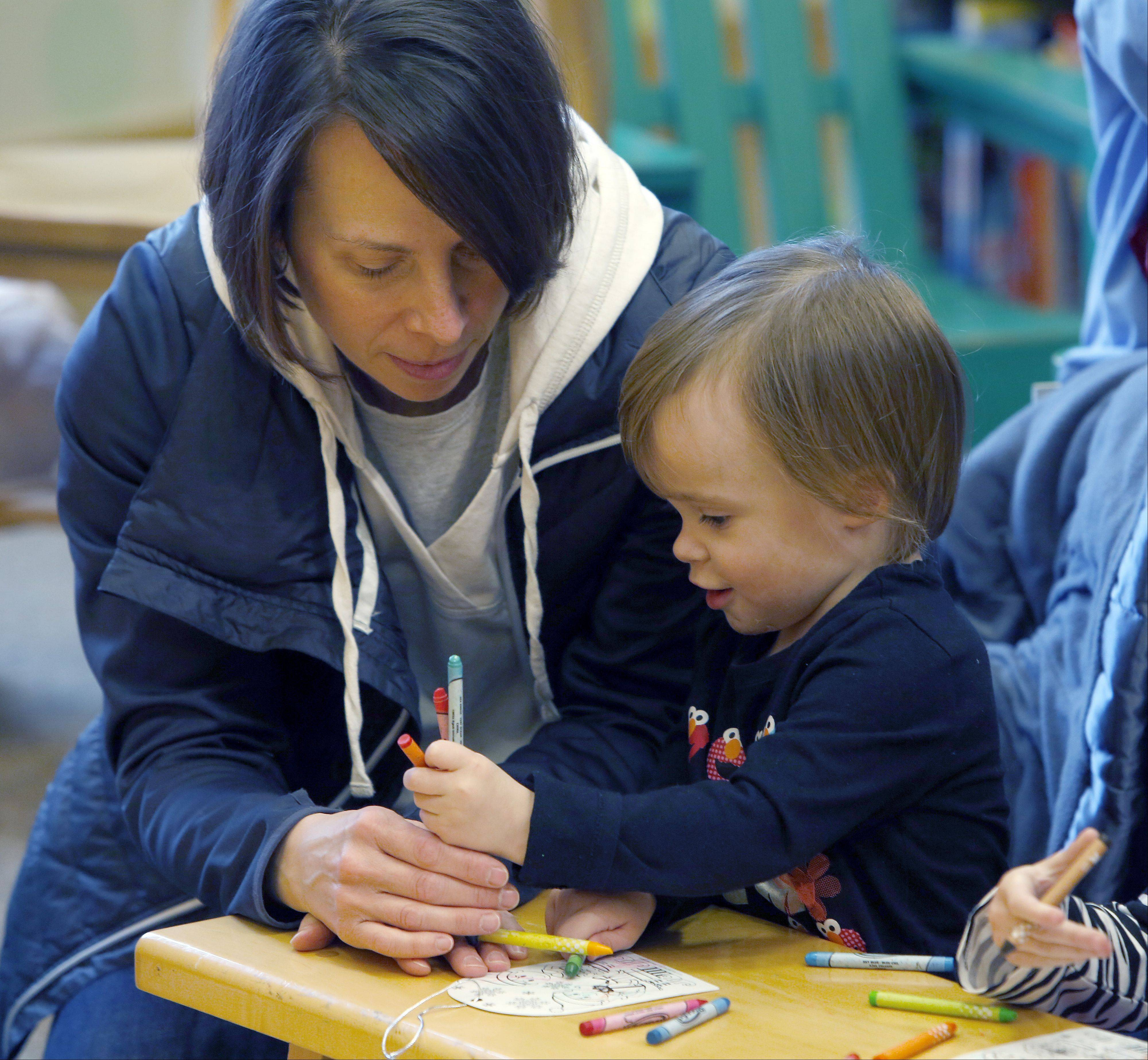 Amy Schram of Elgin helps her daughter Molly, 2�, color an ornament during story time Tuesday at the Barnes & Noble at Spring Hill Mall in West Dundee.