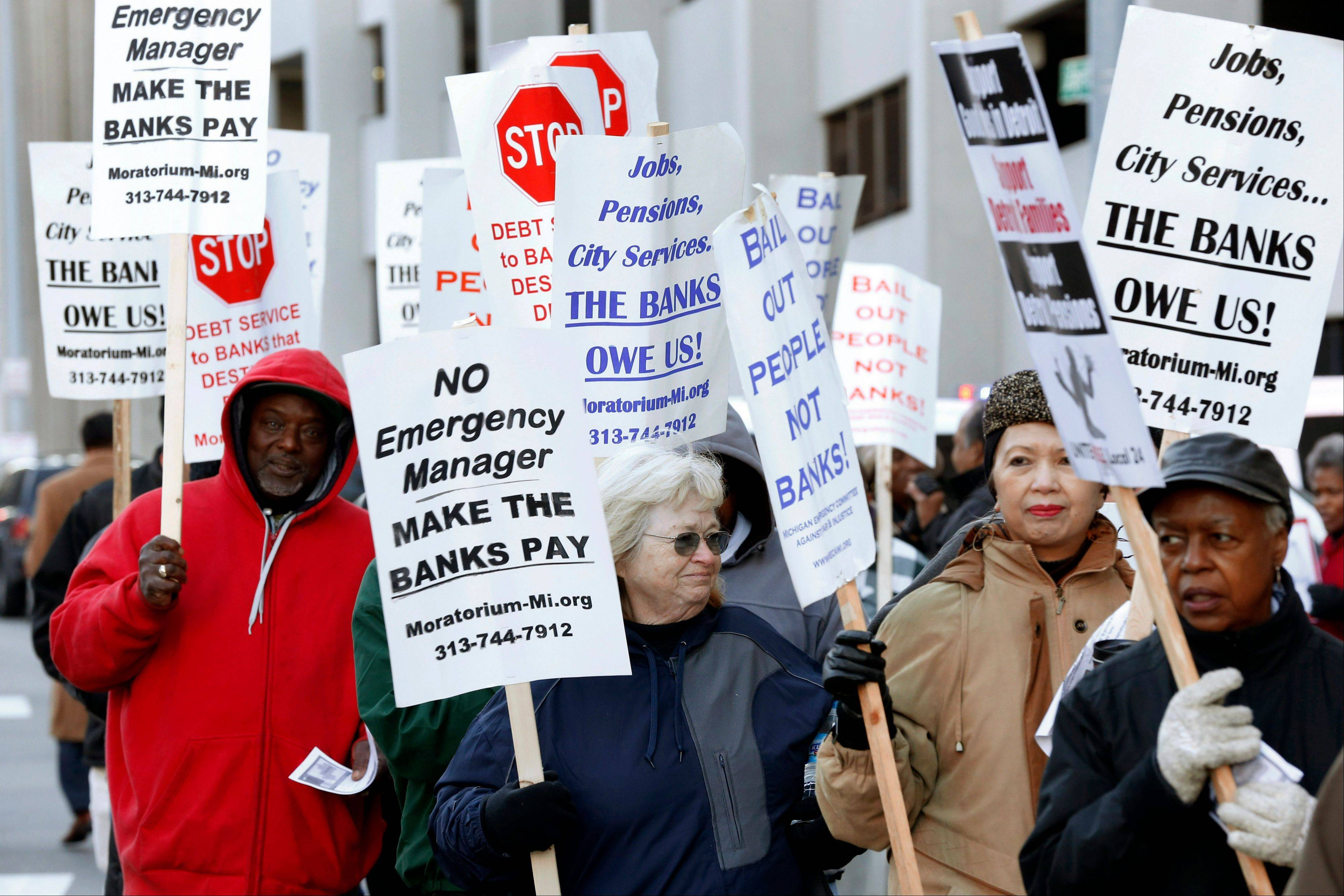 Protesters rally outside federal court in Detroit during a trial to determine if Detroit is eligible to restructure $18 billion in debt. Unions and pensions funds opposed to bankruptcy claim there was a lack of good-faith negotiations with creditors before the Chapter 9 filing.