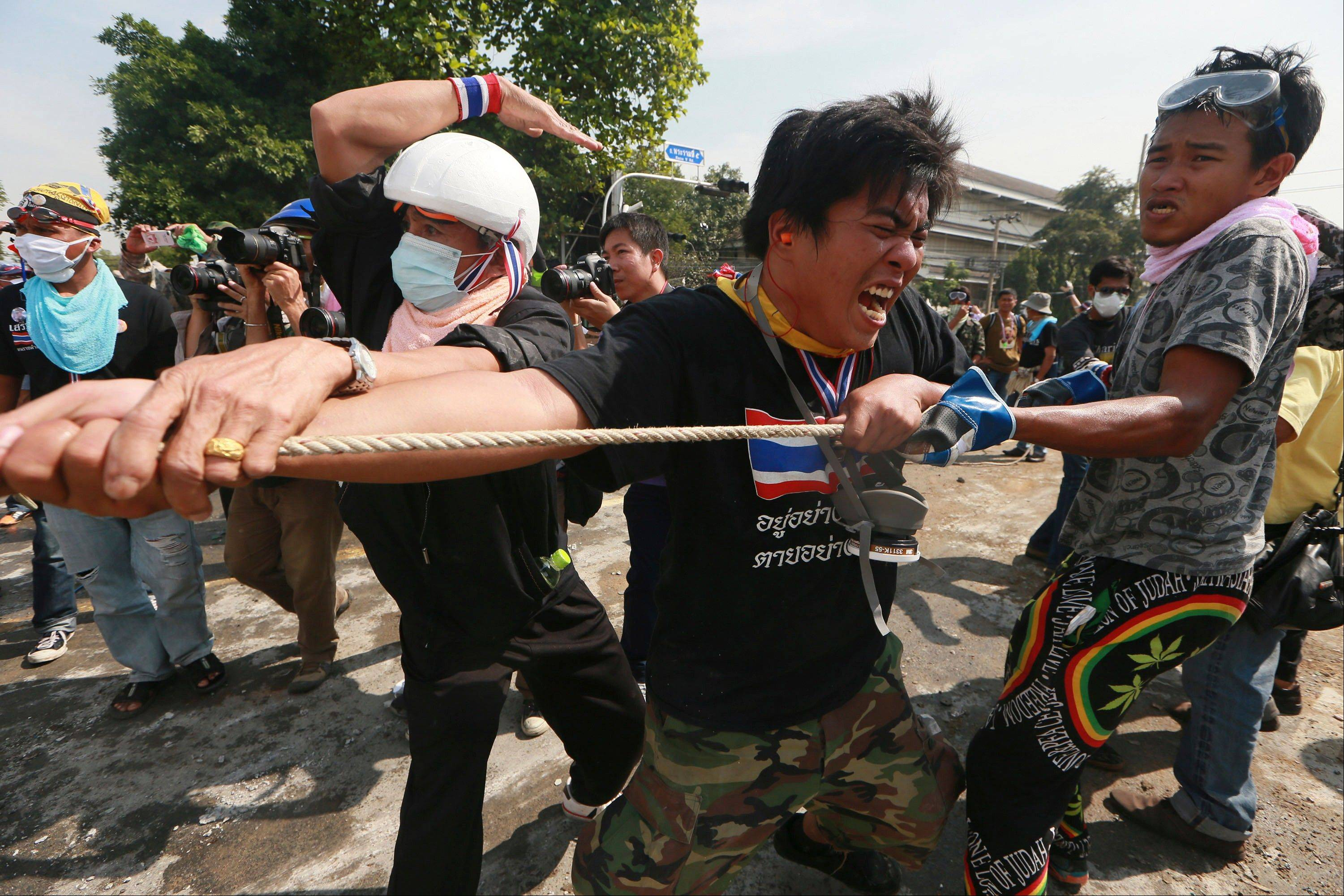 Anti-government protesters remove concrete barriers outside the Government House in Bangkok, Thailand, Tuesday, Dec 3, 2013. Anti-government protesters swarmed into the Thai prime minister�s office compound Tuesday as police stood by and watched, allowing them to claim a symbolic victory after three days of bitter clashes.