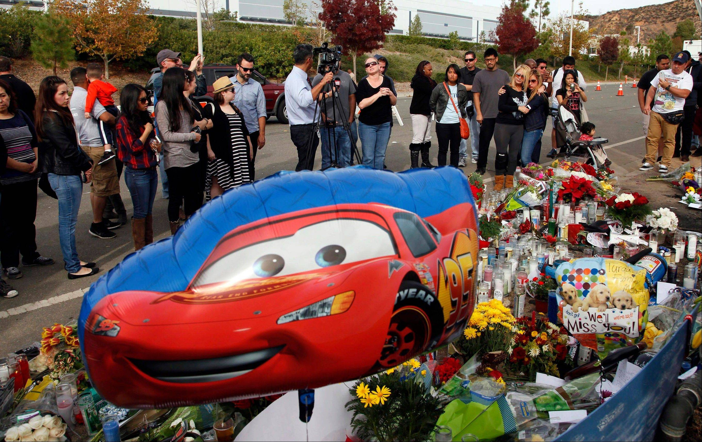 People stand around a roadway memorial Monday at the site of the auto crash that took the life of actor Paul Walker and Roger Rodas in the small community of Valencia, Calif. Walker and Rodas died Saturday when the 2005 Porsche Carrera GT they were traveling in smashed into a light pole and tree.