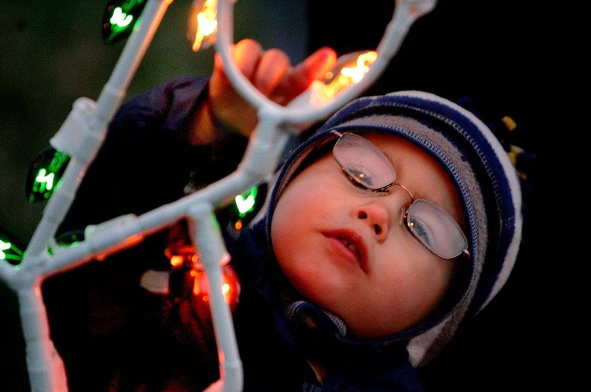 Christian Widelski, 2, of Lake Zurich, touches a light on a decoration at Lake Zurich's annual holiday tree lighting at Breezewald Park. Natural light makes for the best picture so try to avoid using flash at these events and move your subjects closer to the lights or candles. You will have to change your ISO to 1600 or 3200 for the low light exposure.