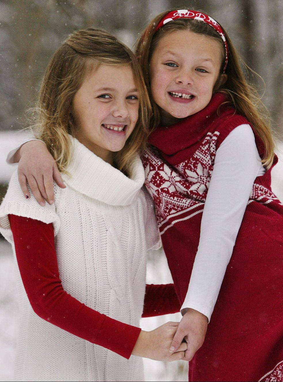 Clare, left, and Addie Hankins pose for a portrait as they play in the snow. It is important to use a lens with a longer focal length, such as a 100 mm or longer, to shoot portraits to soften the background and accentuate the subject.