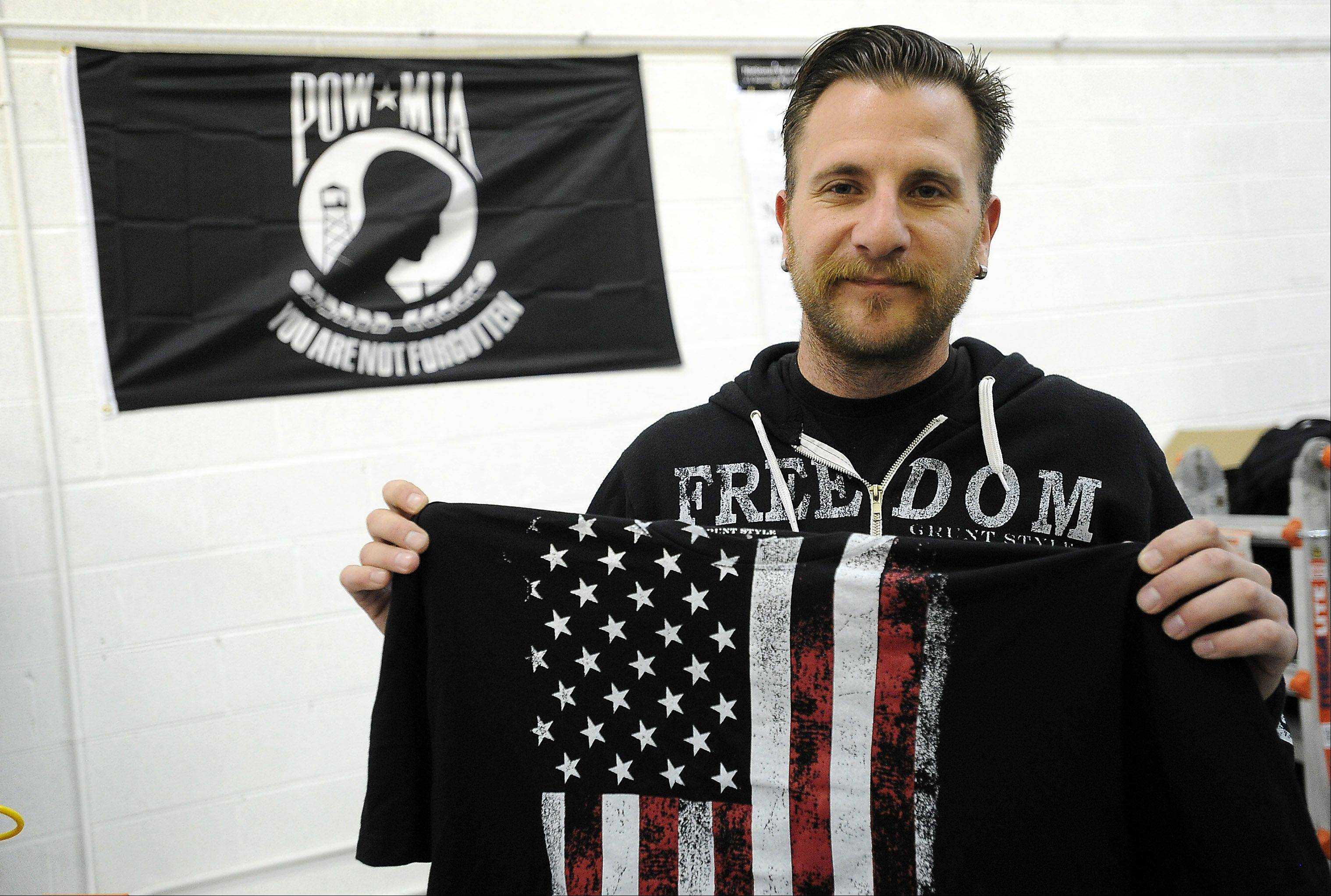 Marine Corps veteran Timothy Jensen of Romeoville holds up a shirt he designed that is one of Grunt Style's more popular items.
