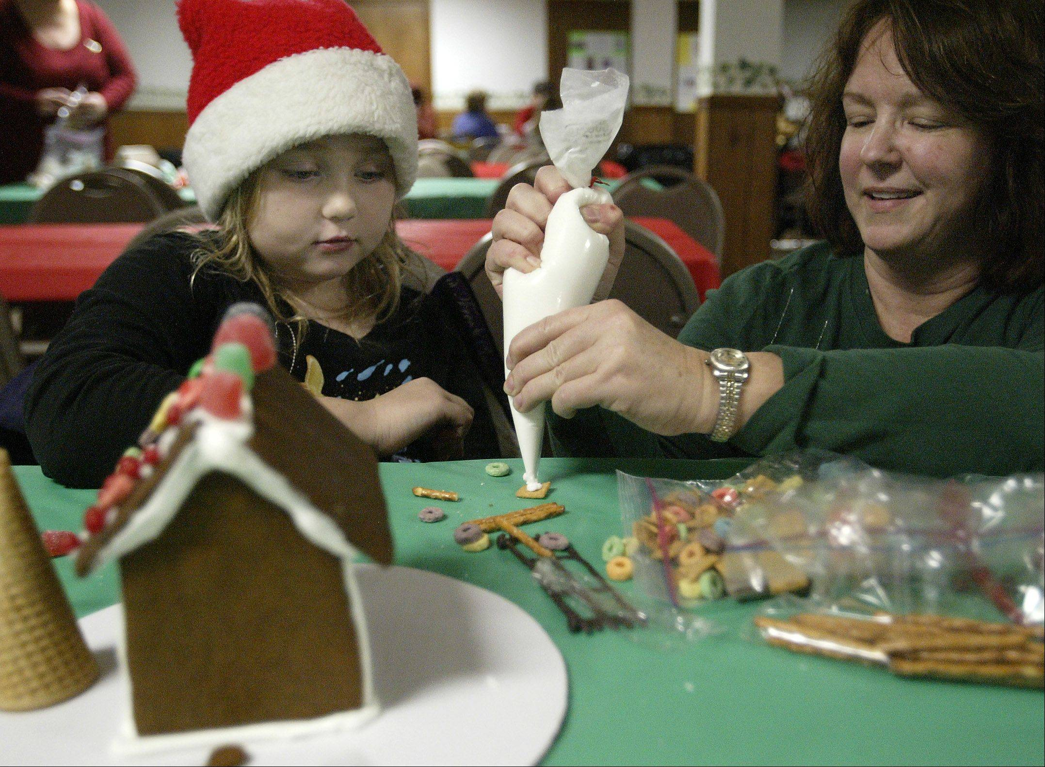 Kylie Marbury-Savage, 7, of West Dundee works on a gingerbread house with her grandmother, Charisse Marbury of Carpentersville, at a previous Dickens in Dundee festival. Crafts are a part of the annual holiday celebration.