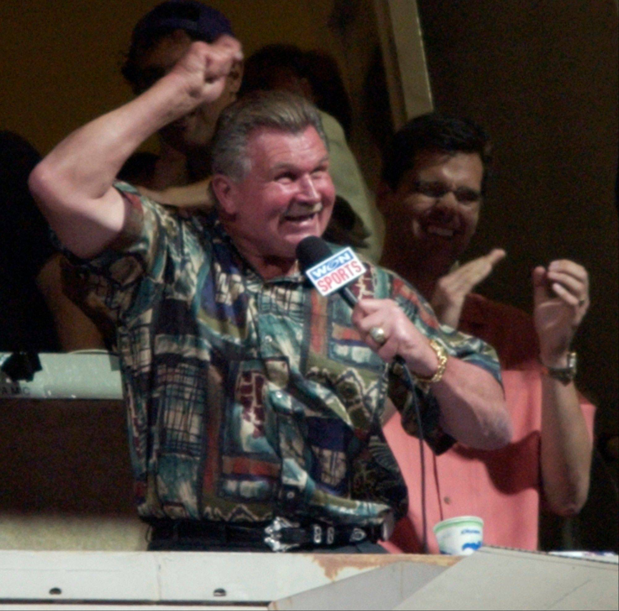 "In a performance hailed as the worst rendition of ""Take Me Out to the Ball Game"" in Wrigley Field history, a frenetic Mike Ditka rushes through the lyrics during the 7th-inning stretch at a Cubs game in 2002."