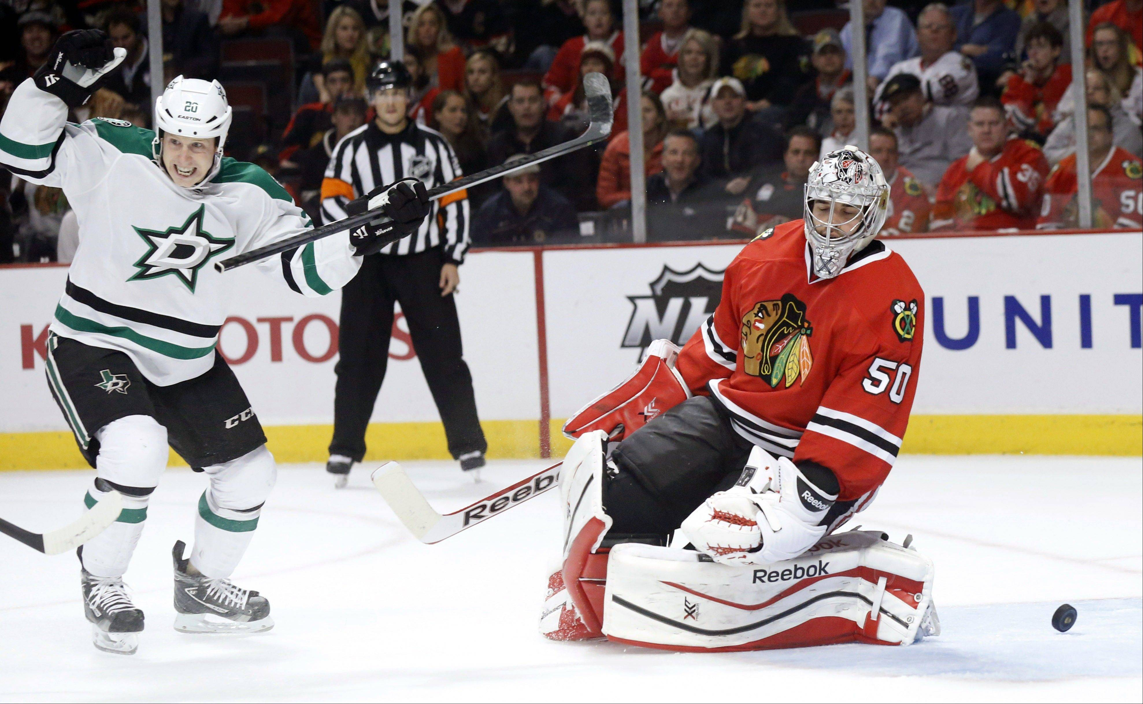 Stars center Cody Eakin, left, celebrates Valeri Nichushkin's goal as the puck bounces back out of the net behind Chicago Blackhawks goalie Corey Crawford during the first period of an NHL hockey game Tuesday, Dec. 3, 2013, in Chicago.