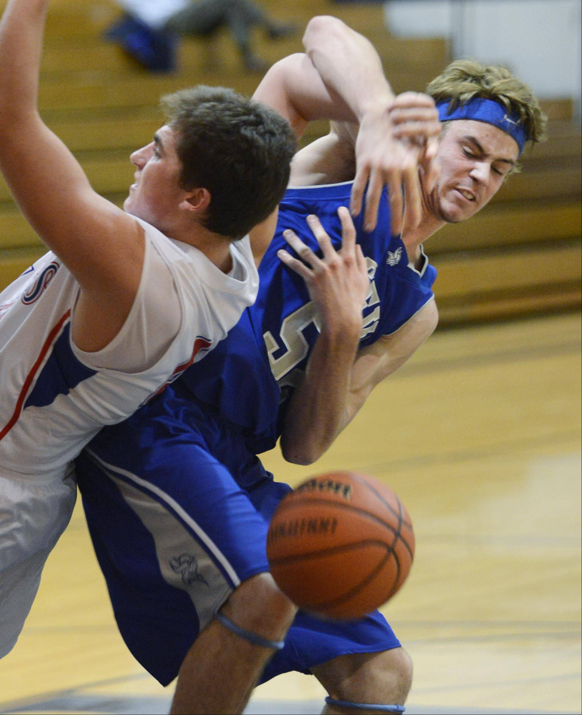 Geneva's Mike Landi, right, and Marmion Academy's Danny Bicknell tangle under the basket Monday in the Wildcat Turkey Classic in West Chicago.