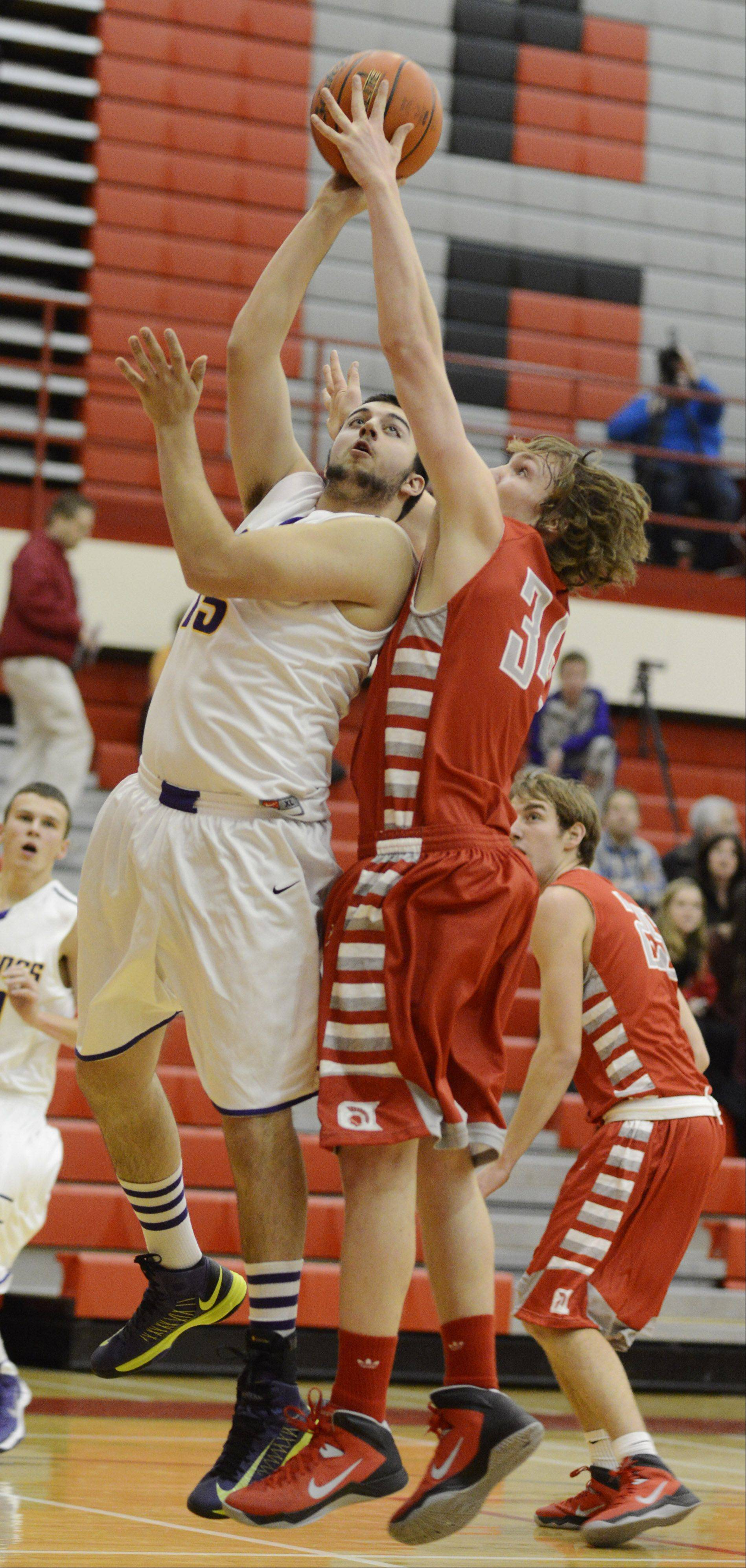 Rolling Meadows' Terry Moran, left, takes a shot against Deerfield's Michael Alfieri during Tuesday's game in Palatine.