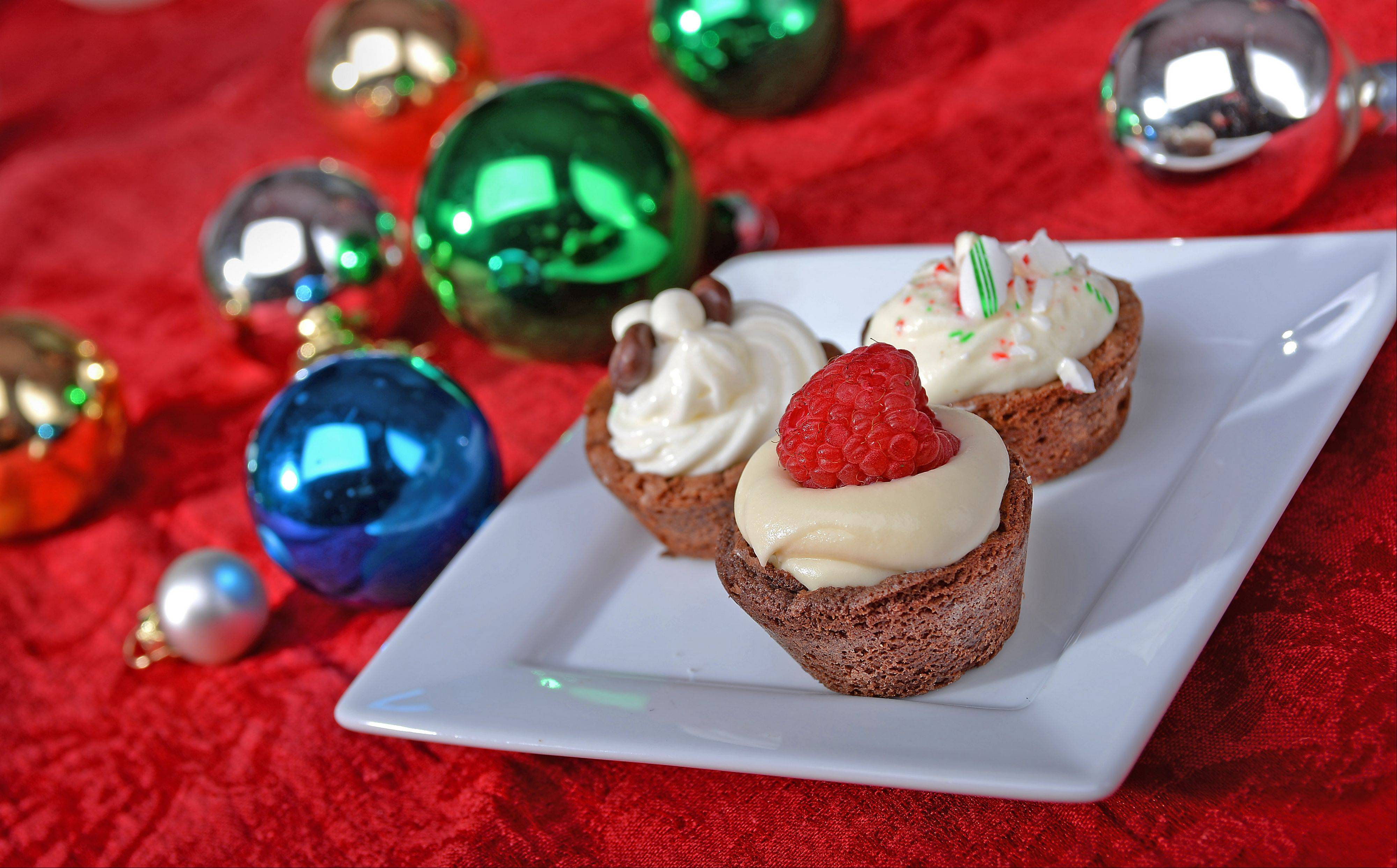 Brownie bites topped with mousse and garnished with raspberries and crushed candy canes are a welcome addition to any holiday treat table.