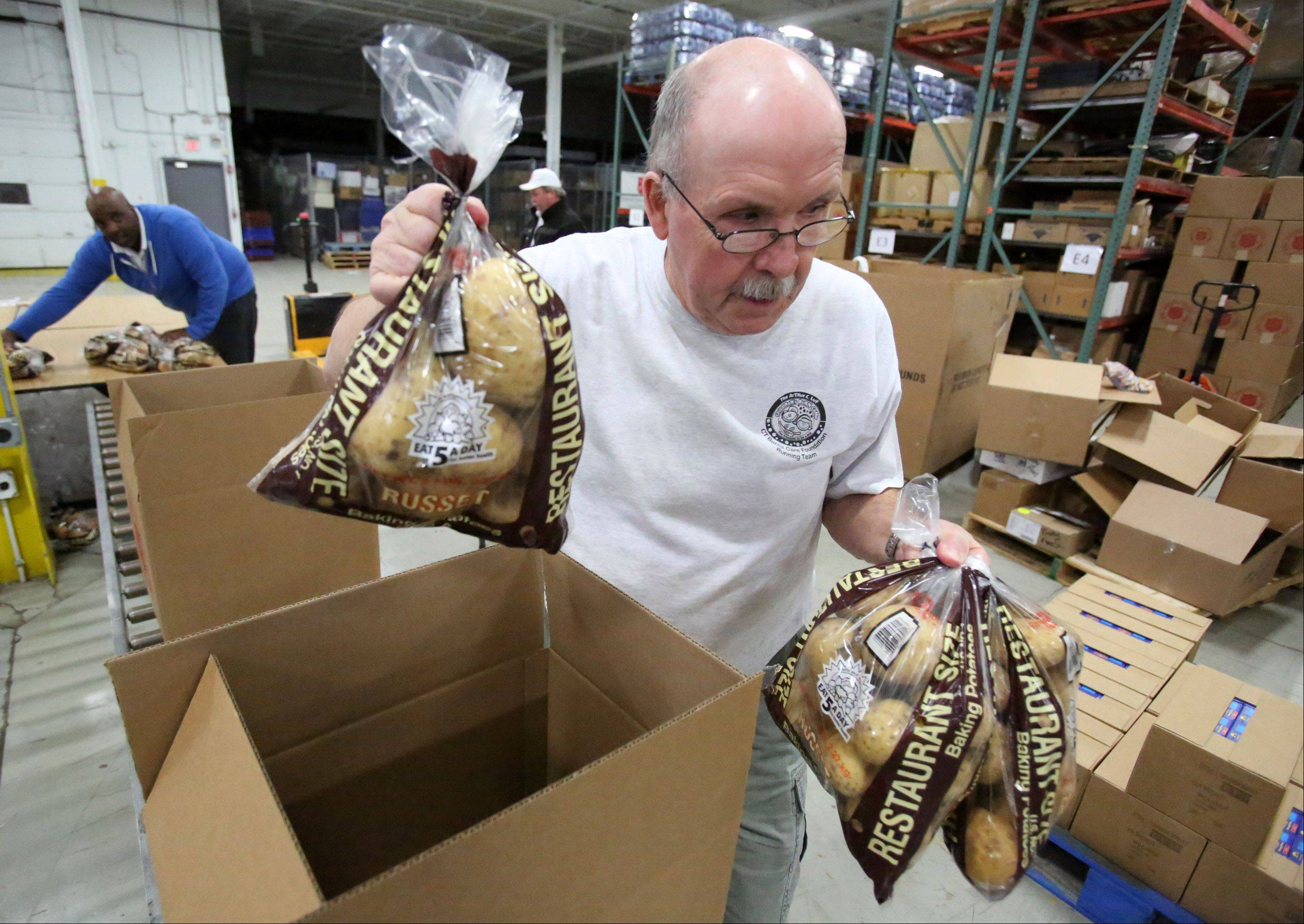 Volunteer Larry Moe of Elk Grove Village packs potatoes into food boxes Wednesday, part of an effort to prepare more than 10,000 Christmas Christmas food boxes containing fresh potatoes, corn, green beans, cranberry sauce, yams, gravy and stuffing at the Salvation Army�s Disaster Services Headquarters in Elk Grove Village.