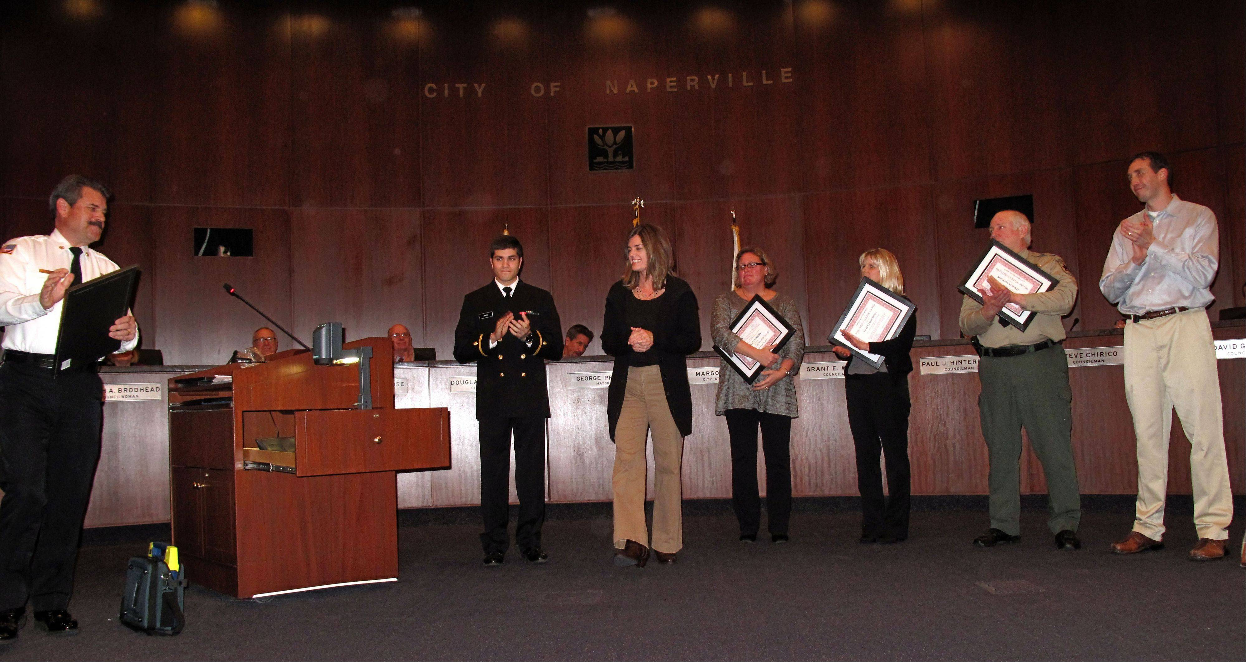 Naperville fire Chief Mark Puknaitis recognizes several nurses, a park district police officer and a Navy reservist for helping save the life of Steve Sloma of Geneva, far right, who went into sudden cardiac arrest around Mile 6 of the half marathon during the inaugural Edward Hospital Naperville Marathon on Nov. 10. Those recognized Tuesday include Yousef Ahmed, Stephanie Chang, Merri Lazenby, Traci Iarrobino and Michael Kurinec.