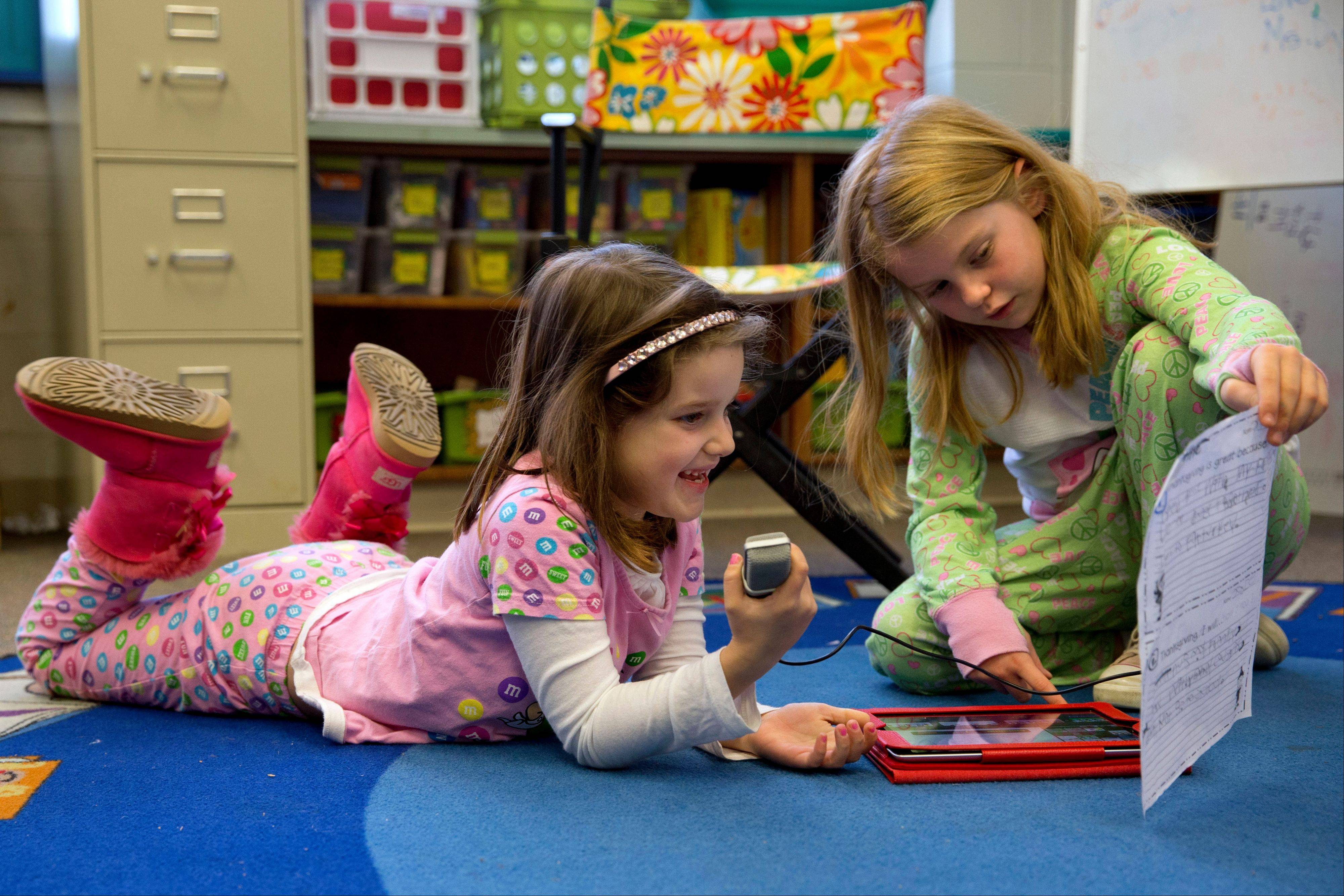 Josie Barton, 7, left, records audio into an iPad for an iMovie project with classmate Marin Peale, 7, in their multi-grade first and second grade class at Jamestown Elementary School in Arlington, Va.