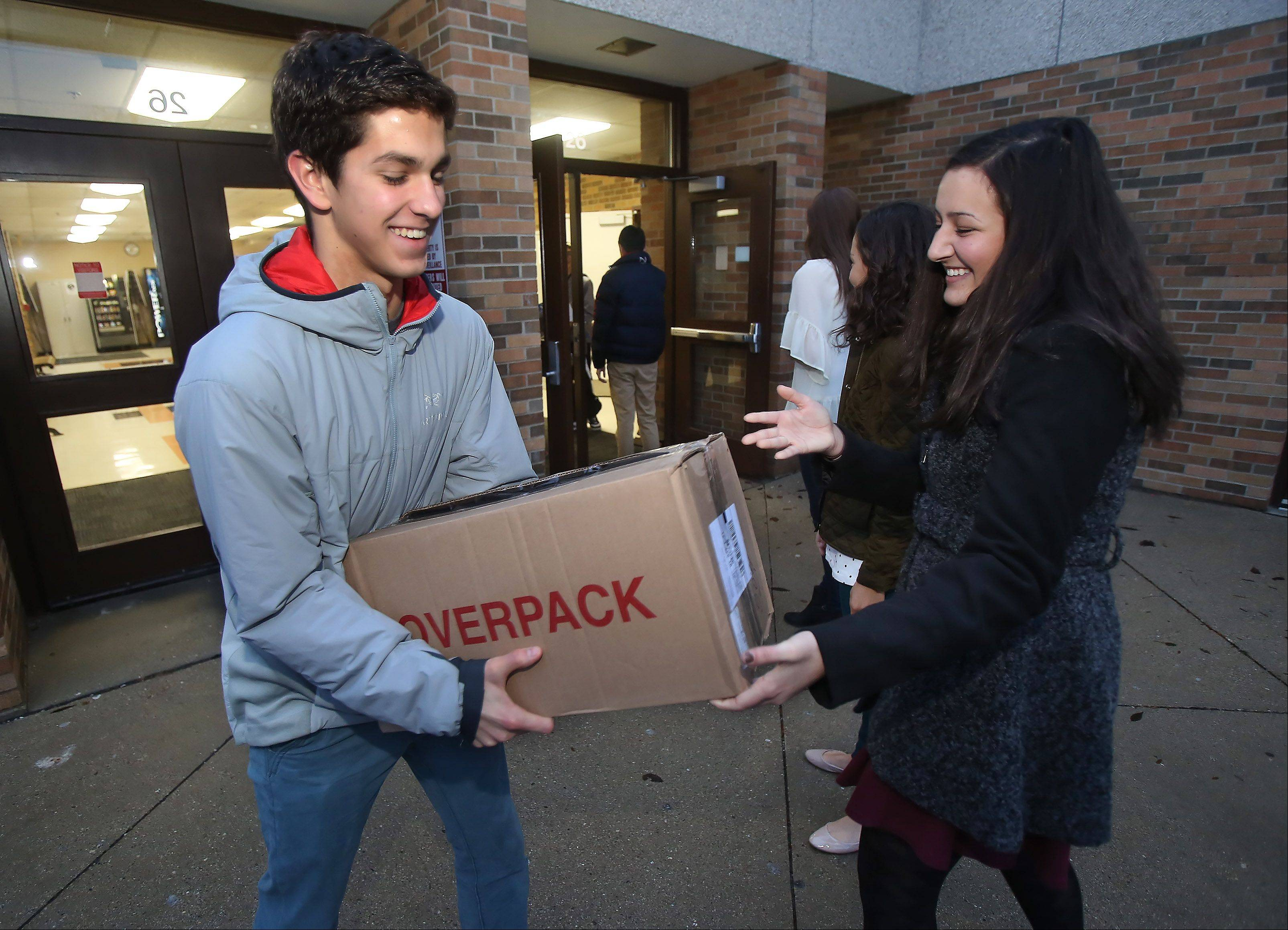 Libertyville High School junior Mark Boynton receives a box from Alexandria El Ghatit as they work in a human food chain Wednesday morning to load trucks with boxes of canned goods for Libertyville Township food pantry. The student council collected canned goods, paper goods and toiletries and monetary donations for the food pantry and other organizations.