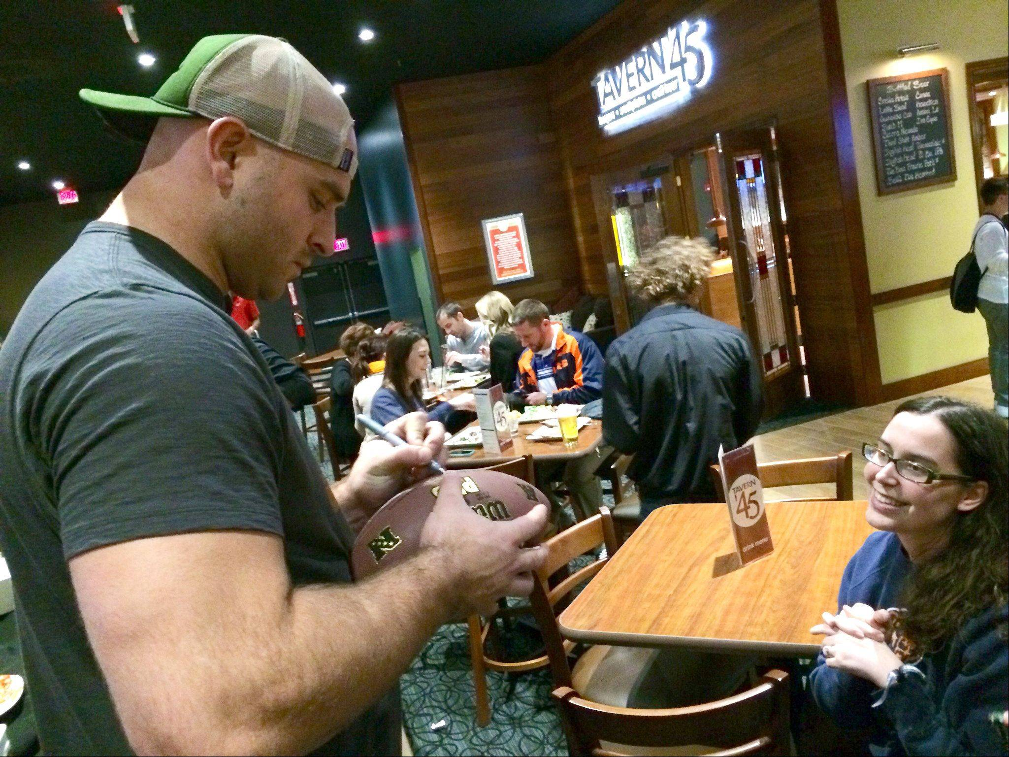 Chicago Bear Kyle Long signs a football for a fan at a charity bowling event in Buffalo Grove Tuesday night.