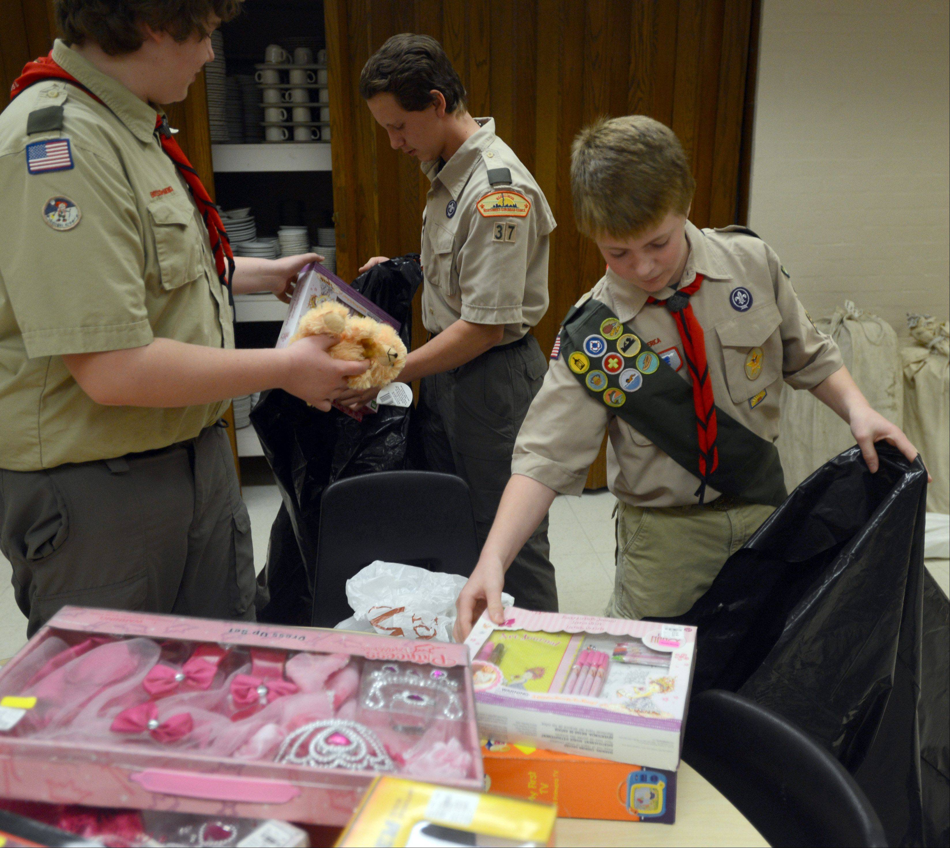 Troop 37 members from left, Arthur Gasey, 13, of Arlington Heights, Herby Savage, 14, of Schaumburg, and Max Kron, 14, of Mount Prospect pack toys at St Peter Lutheran School in Arlington Heights on Monday night. Troop 37 works with The 100 Percent Foundation to secure the toys.