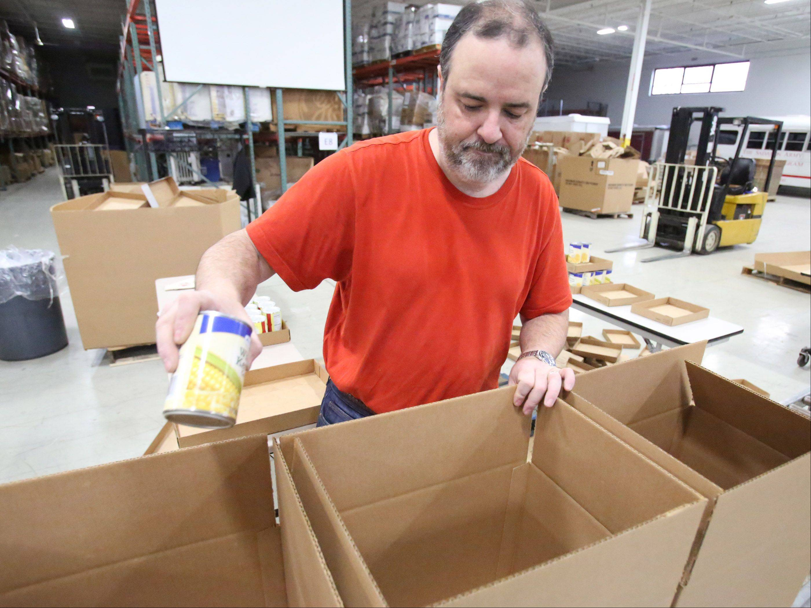 Volunteer Bob Dolan of Hinsdale, who works for Sprint in the Schaumburg area, packs canned vegetables into food boxes Wednesday as part of an effort to prepare more than 10,000 Christmas Christmas food boxes containing fresh potatoes, corn, green beans, cranberry sauce, yams, gravy and stuffing at the Salvation Army's Disaster Services Headquarters in Elk Grove Village.