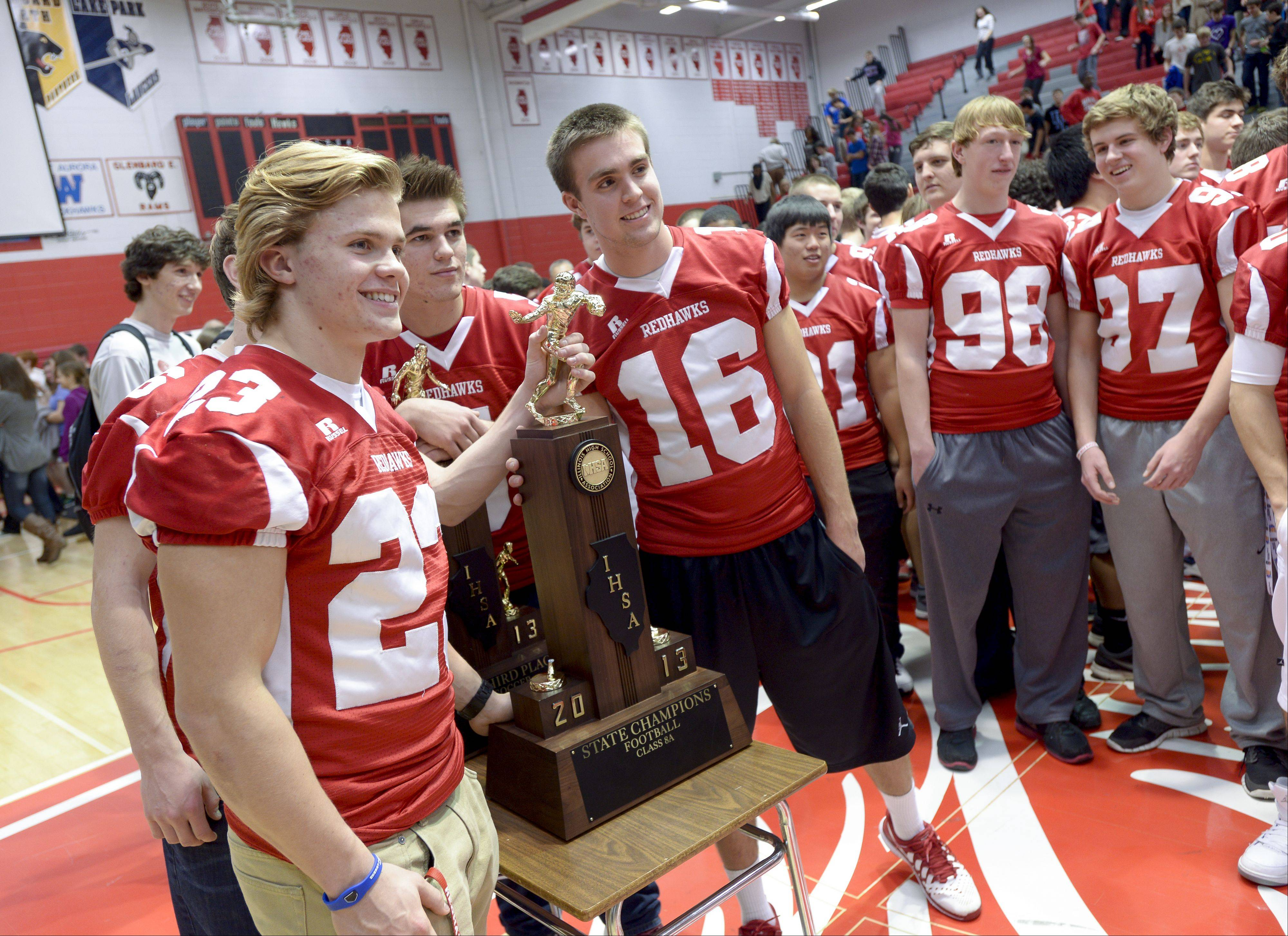 Members of the Naperville Central High School Redhawks football team pose during an assembly Wednesday with the Class 8A state championship trophy they won by beating Loyola 13-10 on Saturday in DeKalb. This is the school's second football championship and its first since 1999.
