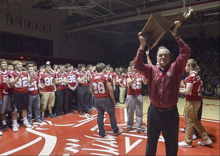 Naperville Central High School Principal Bill Wiesbrook hoists the Redhawks' Class 8A state championship football trophy during an assembly Wednesday at the school in Naperville.