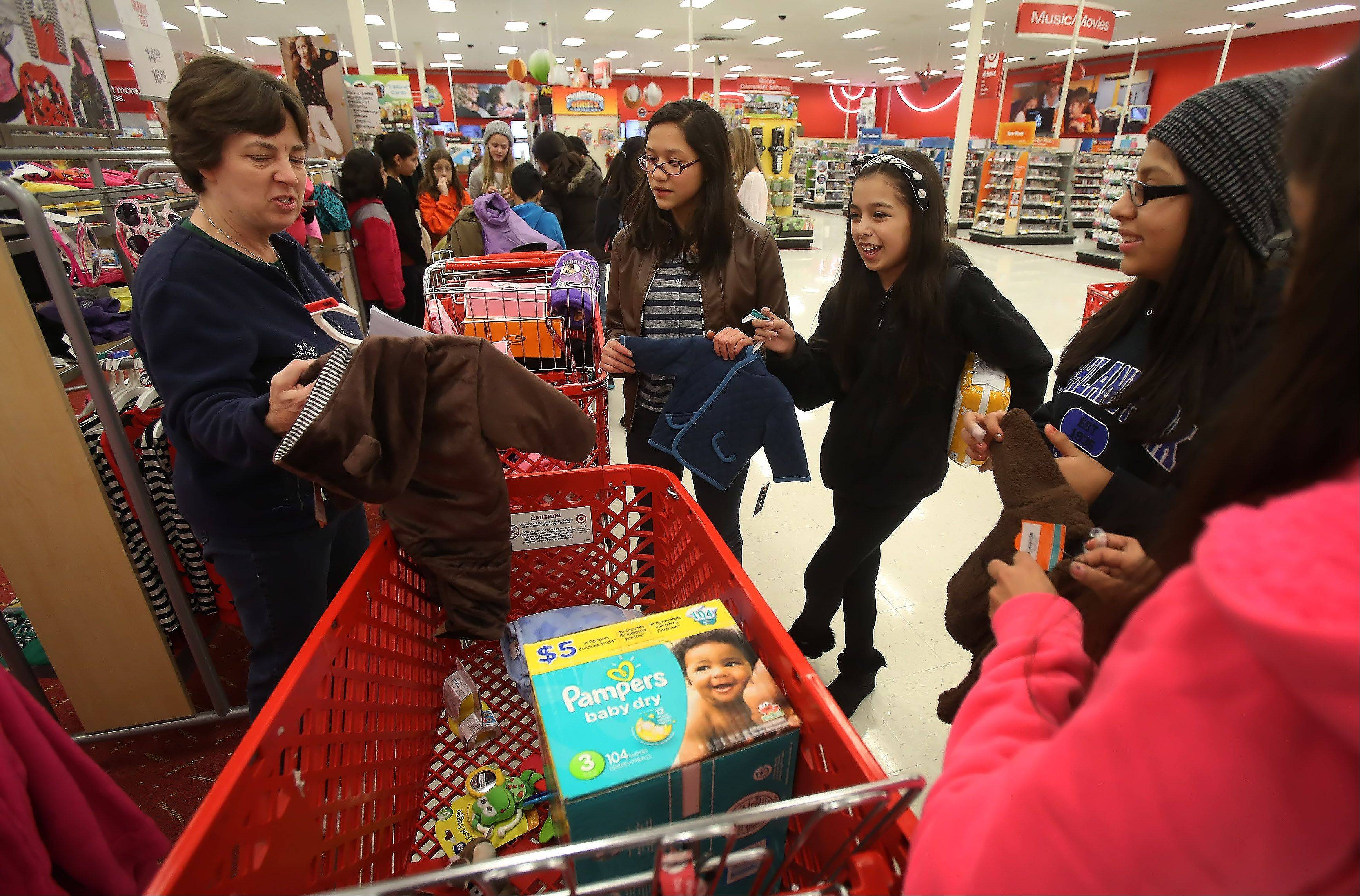 Teacher Gretchen Garza talks with Carl Sandburg Middle School students about the cost of toys and clothing purchased at Target in Mundelein for a needy family. The school's Community Service Club raised $333 to help the family for the holidays.