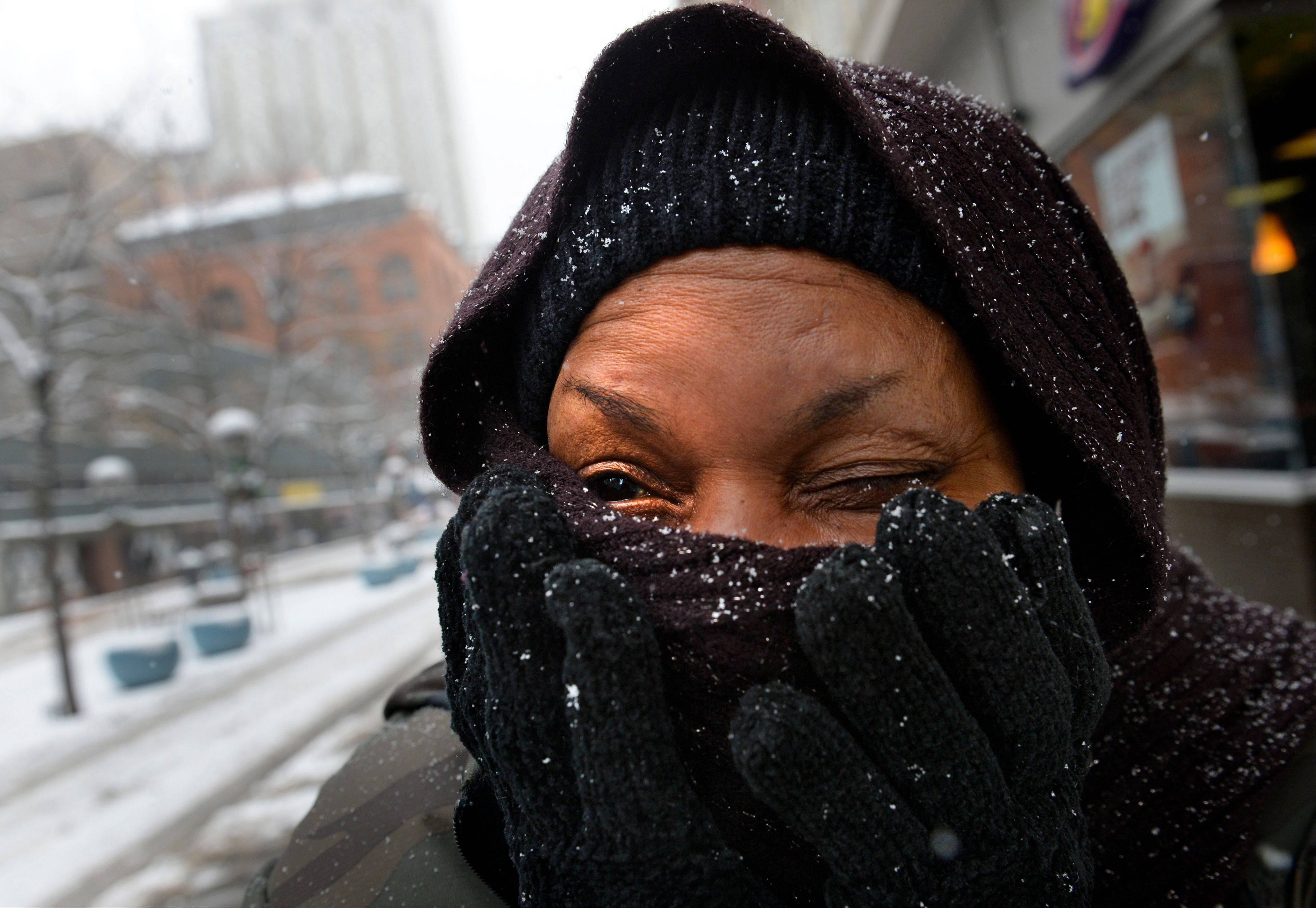 Mary Harts tries to keep warm as she walks in Denver on Tuesday. A wintry storm pushing through the Rockies and Midwest is bringing bitterly cold temperatures and treacherous driving conditions.