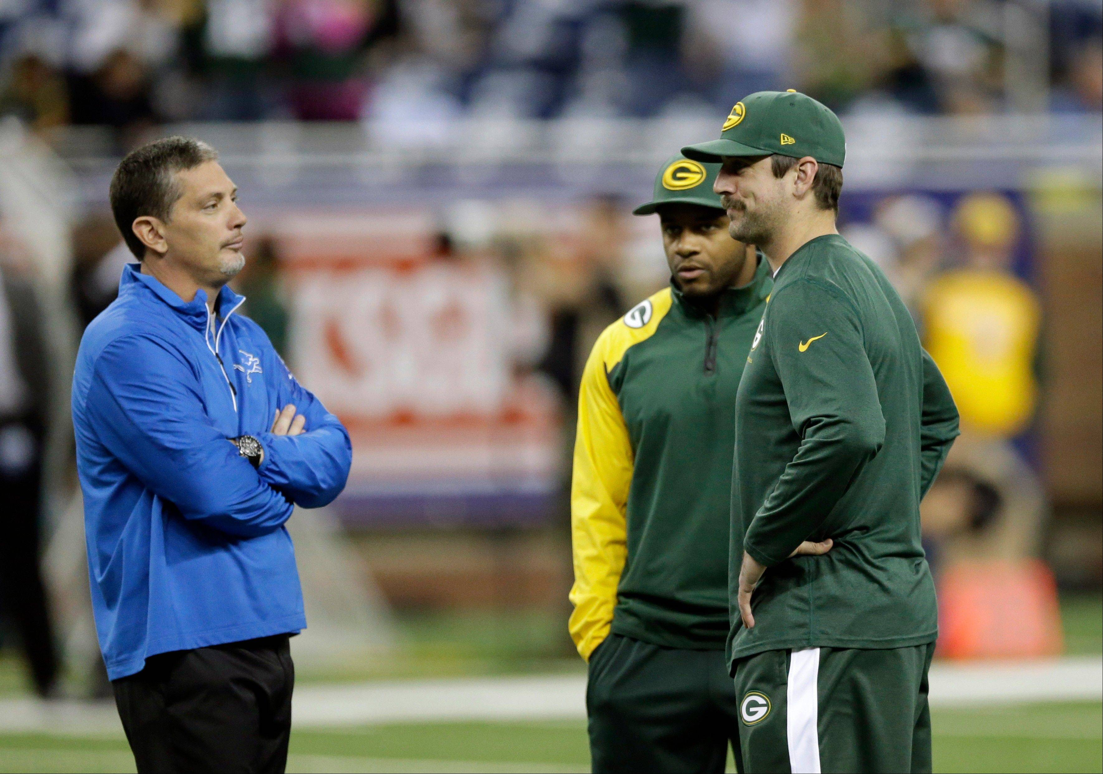 Jim Schwartz, left, talks with Packers wide receiver Randall Cobb, center, and quarterback Aaron Rodgers before Detroit beat Green Bay 40-10 on Thanksgiving.