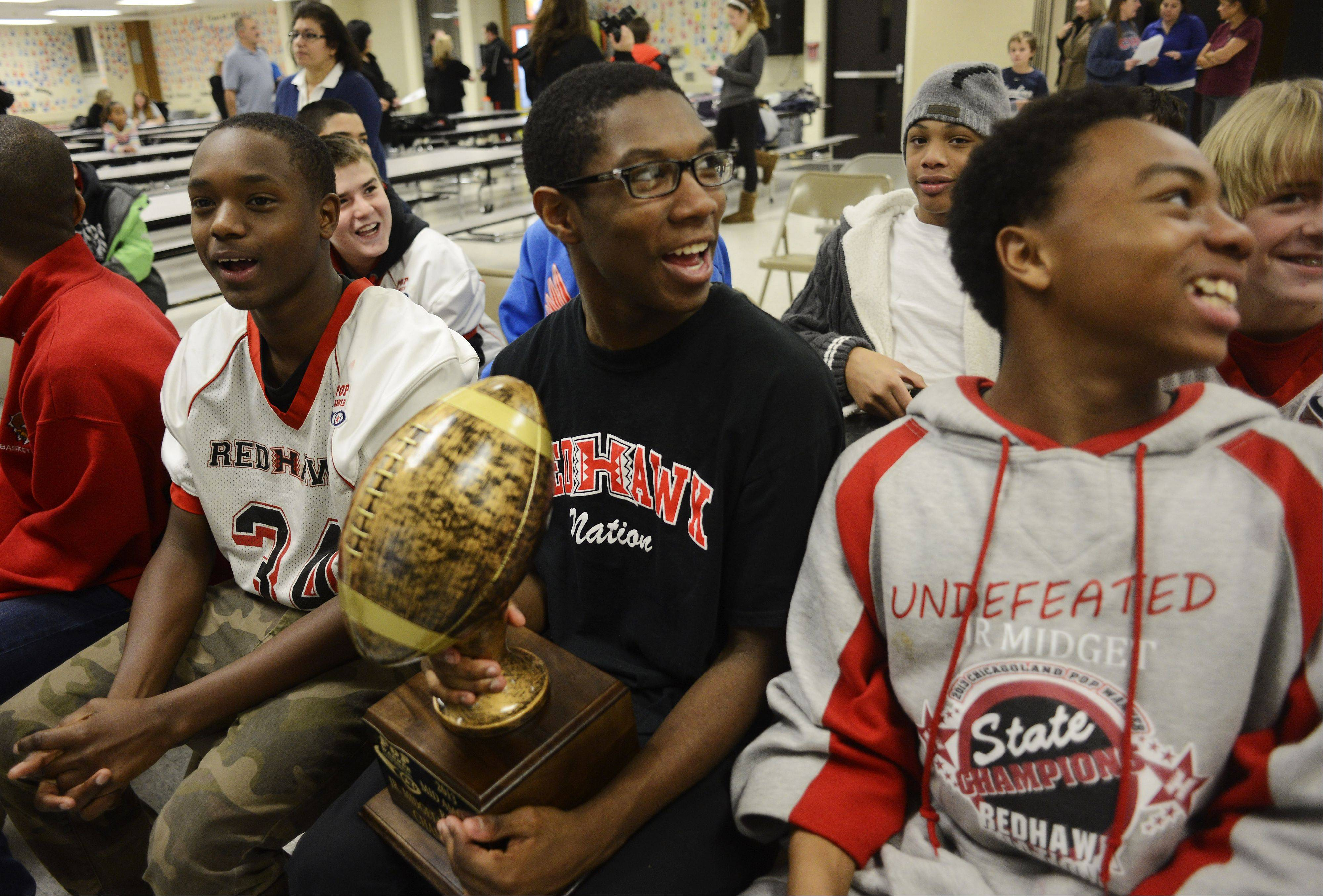 Khalen Young, 14, of Hoffman Estates holds the Hoffman Estates Junior Midget team regional championship trophy while seated with Clevontae Jackson, left, and JJ Daniels as the team waits to find out what team they will be facing in the Pop Warner finals in Orlando.