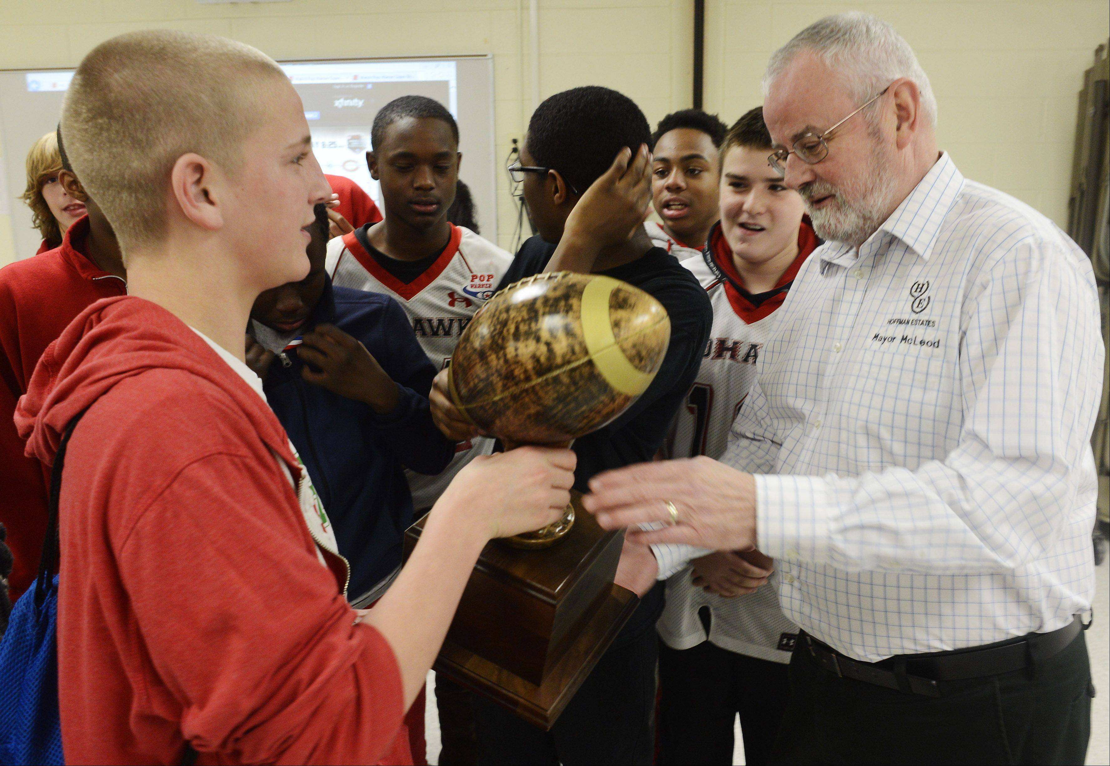 Hoffman Estates Junior Midget quarterback Austin Coalson, 14, of Schaumburg, shows the team's regional championship trophy to Hoffman Estates Mayor William McLeod at Tuesday night's meeting to see who they will face in the national championships at the Pop Warner finals in Orlando.