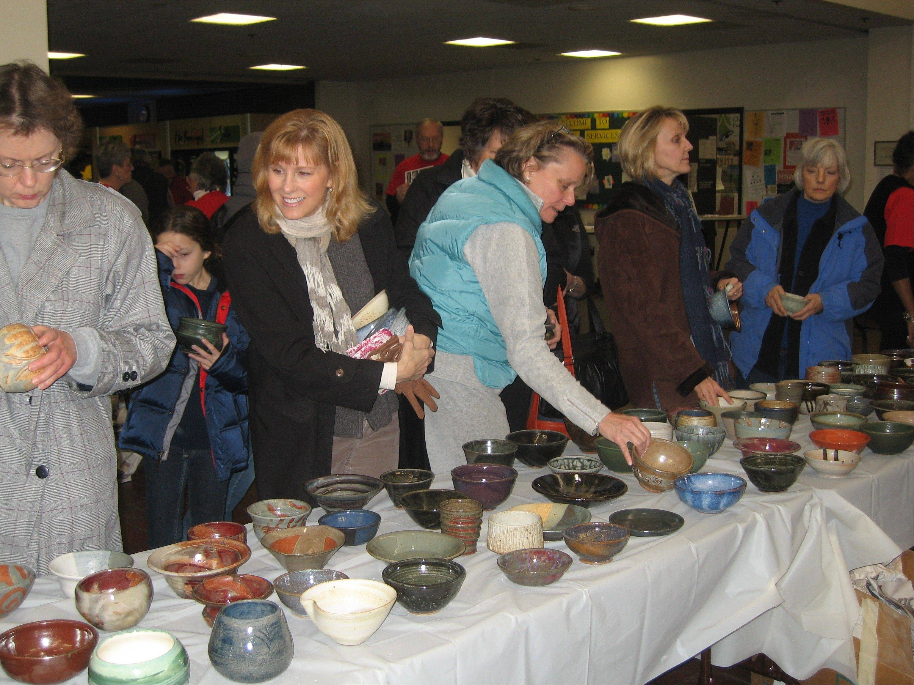 Patrons of last year's Empty Bowls fundraiser at Oakton Community College choose lunch bowls from a wide variety of handcrafted items. The Empty Bowls event celebrates its 10th anniversary on Dec. 7, when Oakton will once again host the fundraiser to raise awareness of worldwide hunger.
