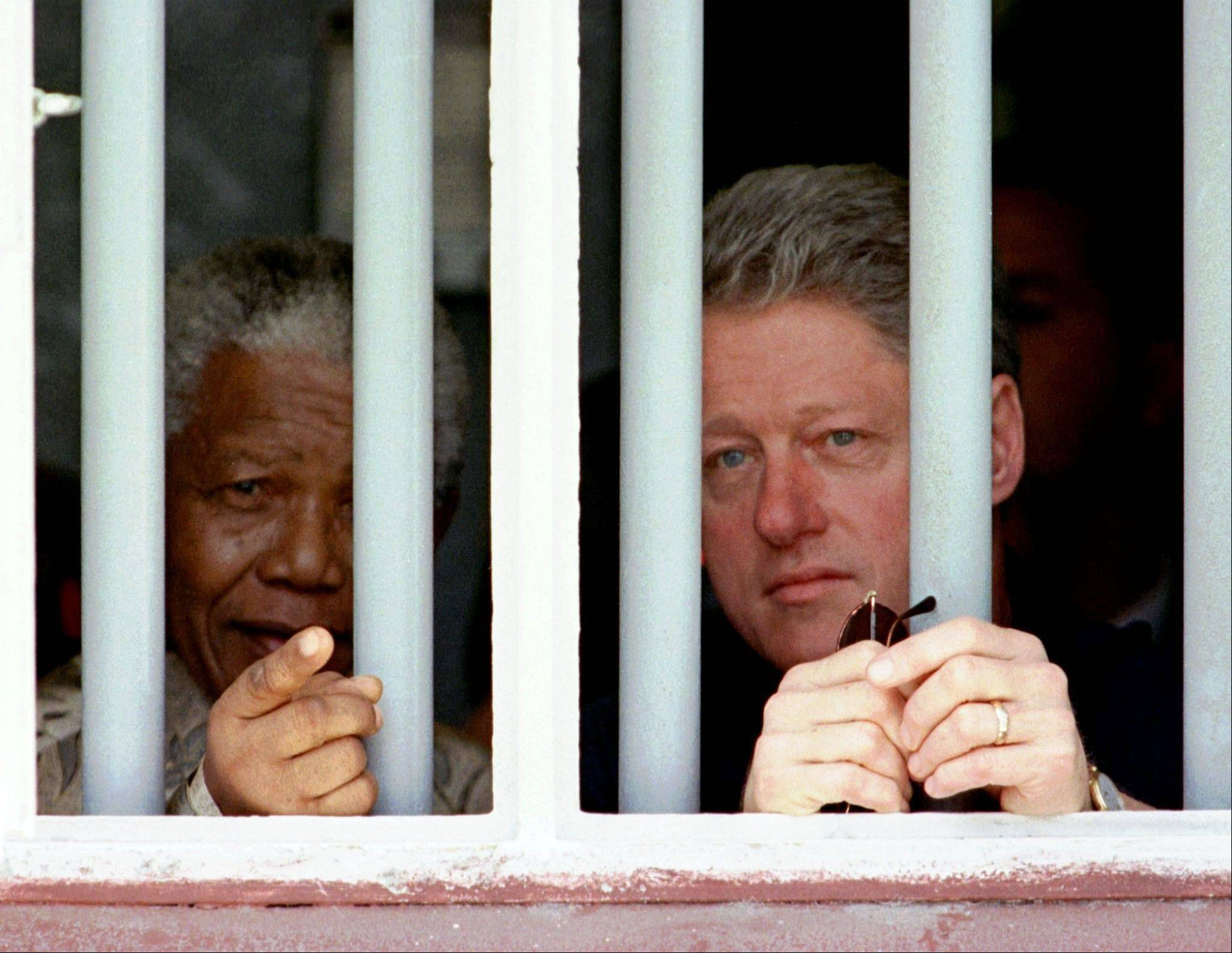 South African President Nelson Mandela, left, and President Bill Clinton peer through the bars of prison cell No. 5, the cramped cell where Mandela was jailed for 18 years in his struggle against apartheid, on Robben Island, South Africa, in this March 27, 1998, file photo.