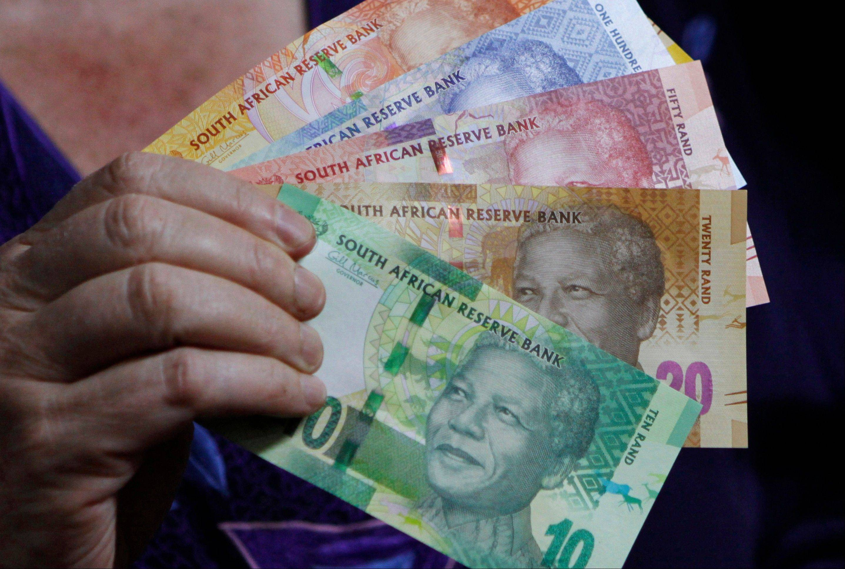Reserve Bank Governor Gill Marcus holds bank notes bearing the image of former President Nelson Mandela in Pretoria, South Africa, in this Nov. 6, 2012 file photo. Across South Africa Mandela�s face is a familiar sight, beaming from T-shirts, drink coasters and bank notes.