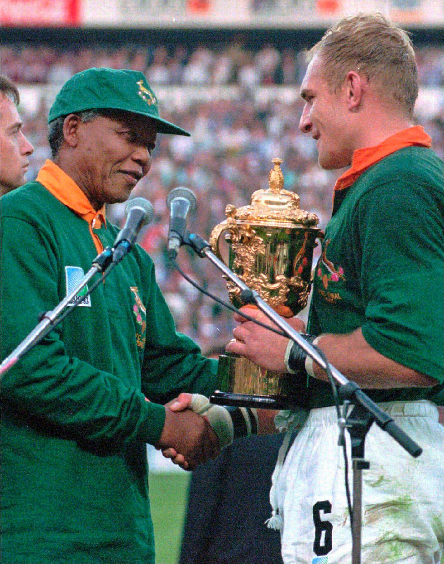 South African rugby captain Francios Pienaar, right, receives the Rugby World Cup from South African President Nelson Mandela, who wears a South African rugby shirt, after they defeated New Zealand in the final June 24, 1995.